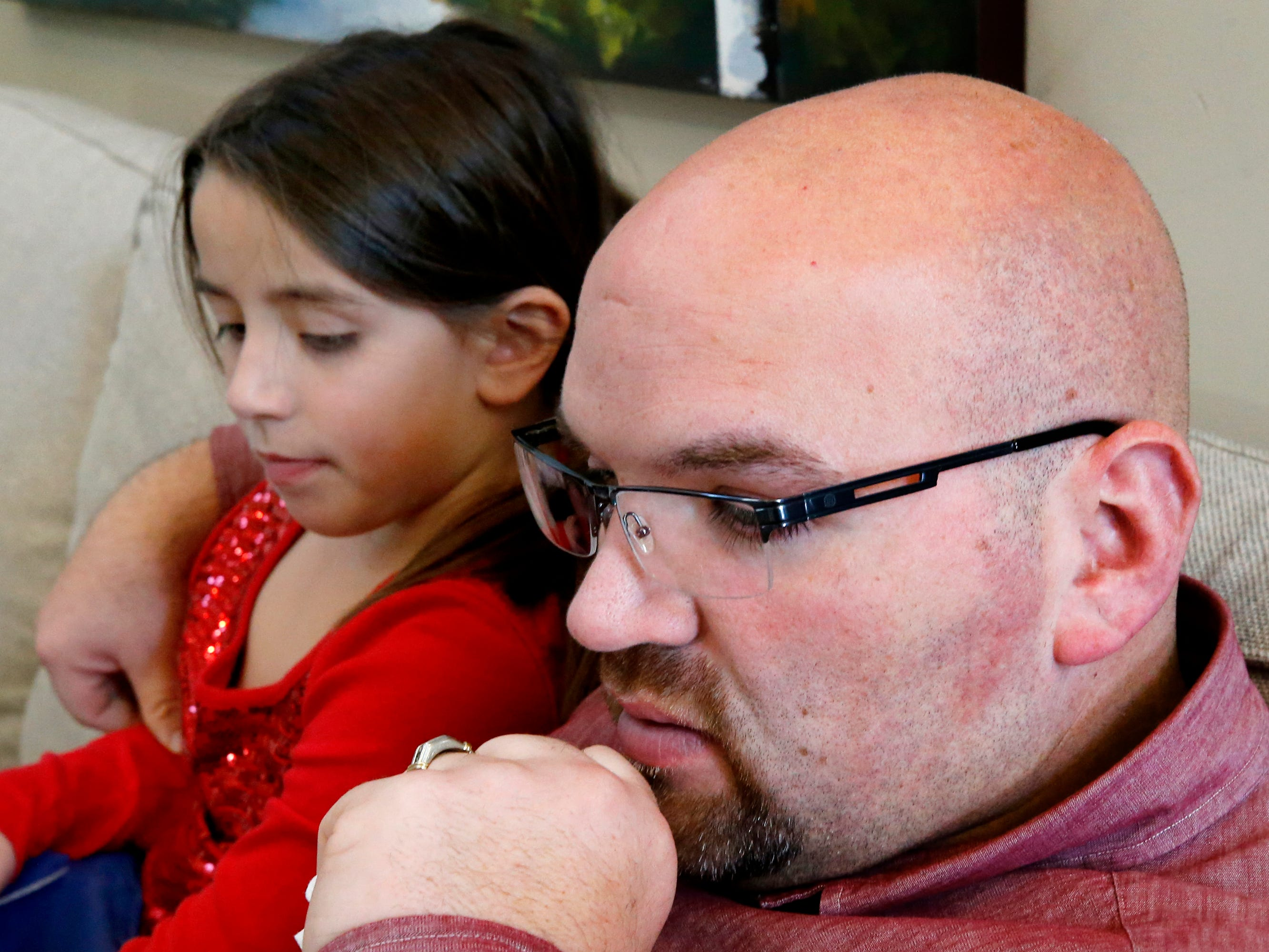 Shane Goddard sits next to his daughter Kayla Goddard, 8, as he talks about being separated from his wife Alma Goddard for a week on Thursday Jan. 10, 2019. Alma Goddard is currently in Mexico and is not being allowed back into the country.