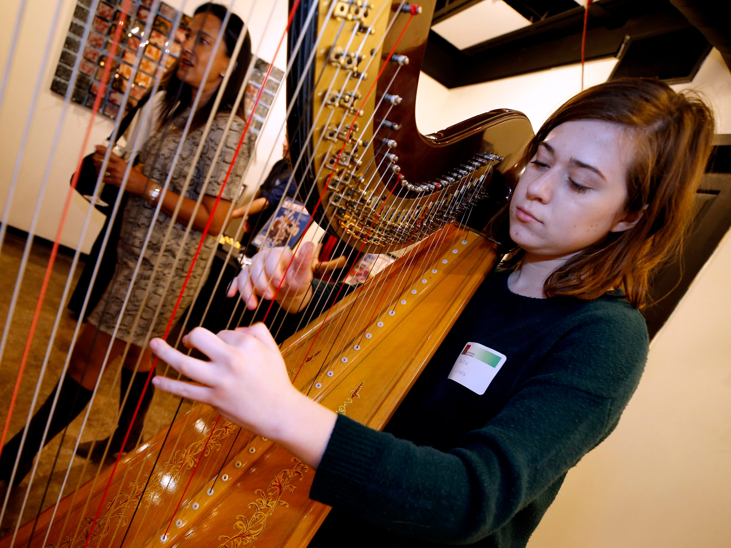 Faith Piers warms up her harp before playing during an arts reception for Rutherford Arts Alliance held at the Center for the Arts on Wednesday Jan. 9, 2019.