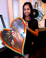Mira Devi Patel shows off her painted heart at an arts reception for Rutherford Arts Alliance that held at the Center for the Arts on Wednesday Jan. 9, 2019.
