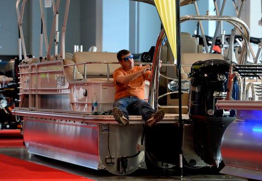 Travis Grishman of Nashville Marine cleans a Sun Catcher G3 pontoon boat in preparation for the Nashville Boat Show at the Music City Center Wednesday, Jan. 9, 2019, in Nashville, Tenn.
