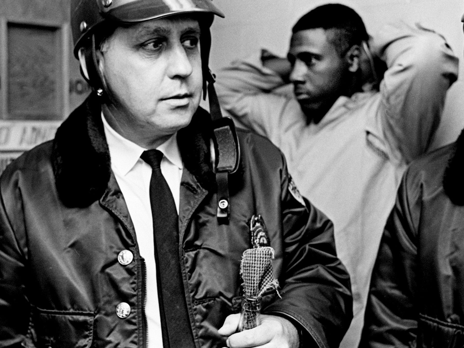 A Metro police officer holds one of the Molotov cocktails confiscated from six men who were taken into custody at 14th Avenue and Himes Street just hours after the Rev. Martin Luther King Jr. was slain in Memphis on April 4, 1968.