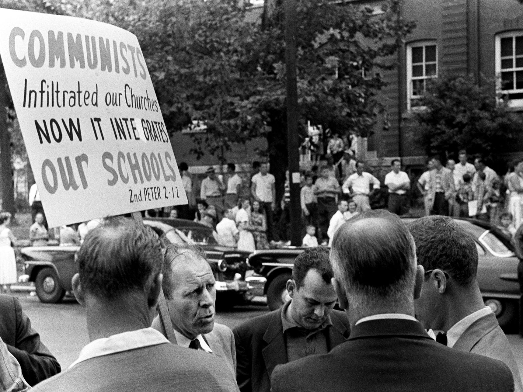 Segregationist the Rev. Fred Stroud, second from left, of Bible Presbyterian Church gathers a crowd to protest integration at Glenn School on Sept. 9, 1957.