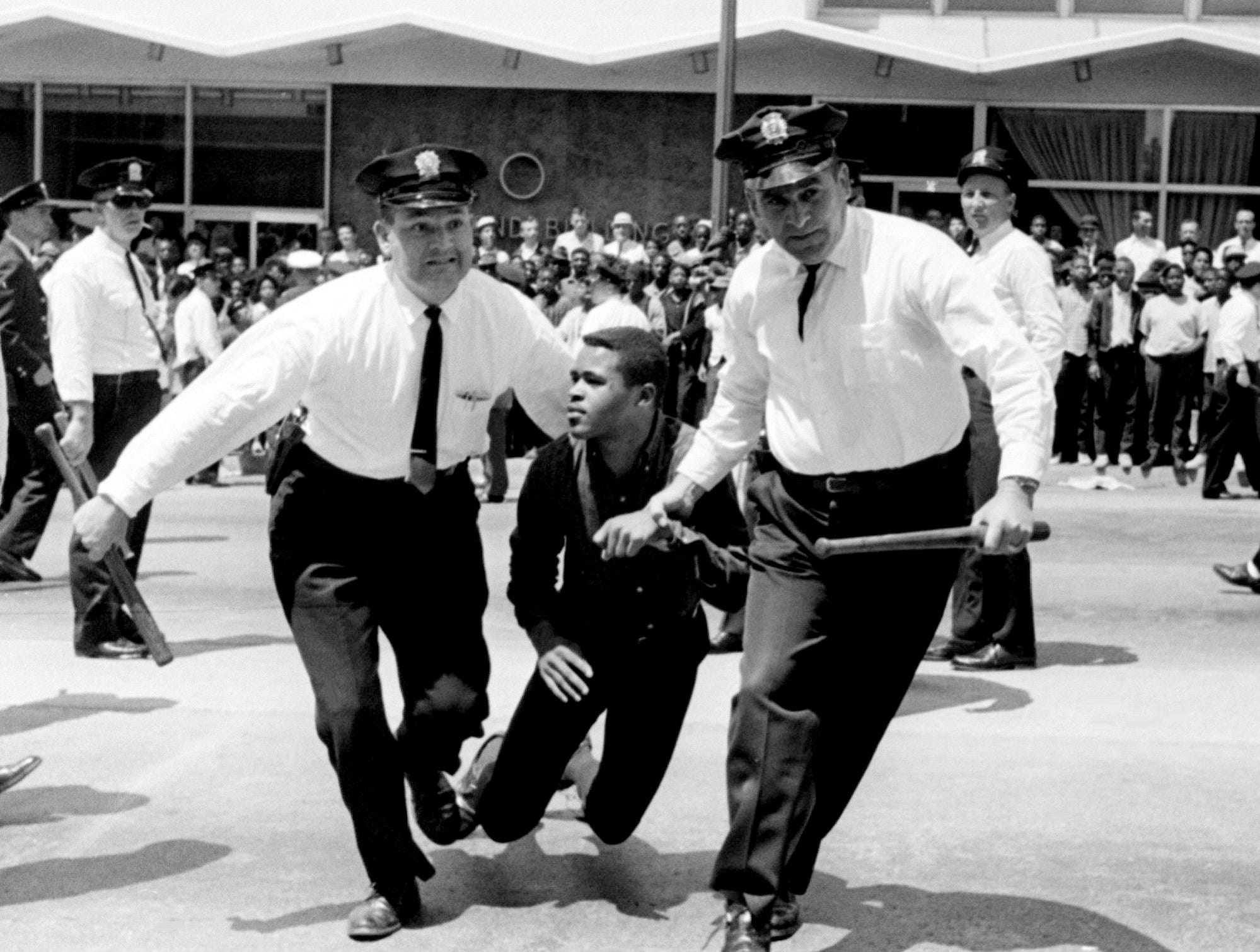 Two Metro police officers drag a civil rights demonstrator out of the middle of West End Avenue toward a police wagon April 29, 1964. He was one of 76 arrested when approximately 300 marchers sat down in the street in front of Morrison's Cafeteria.