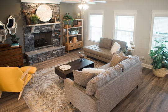 The living area of this Ole South home features a stone fireplace, a ceiling fan and wide-plank flooring.