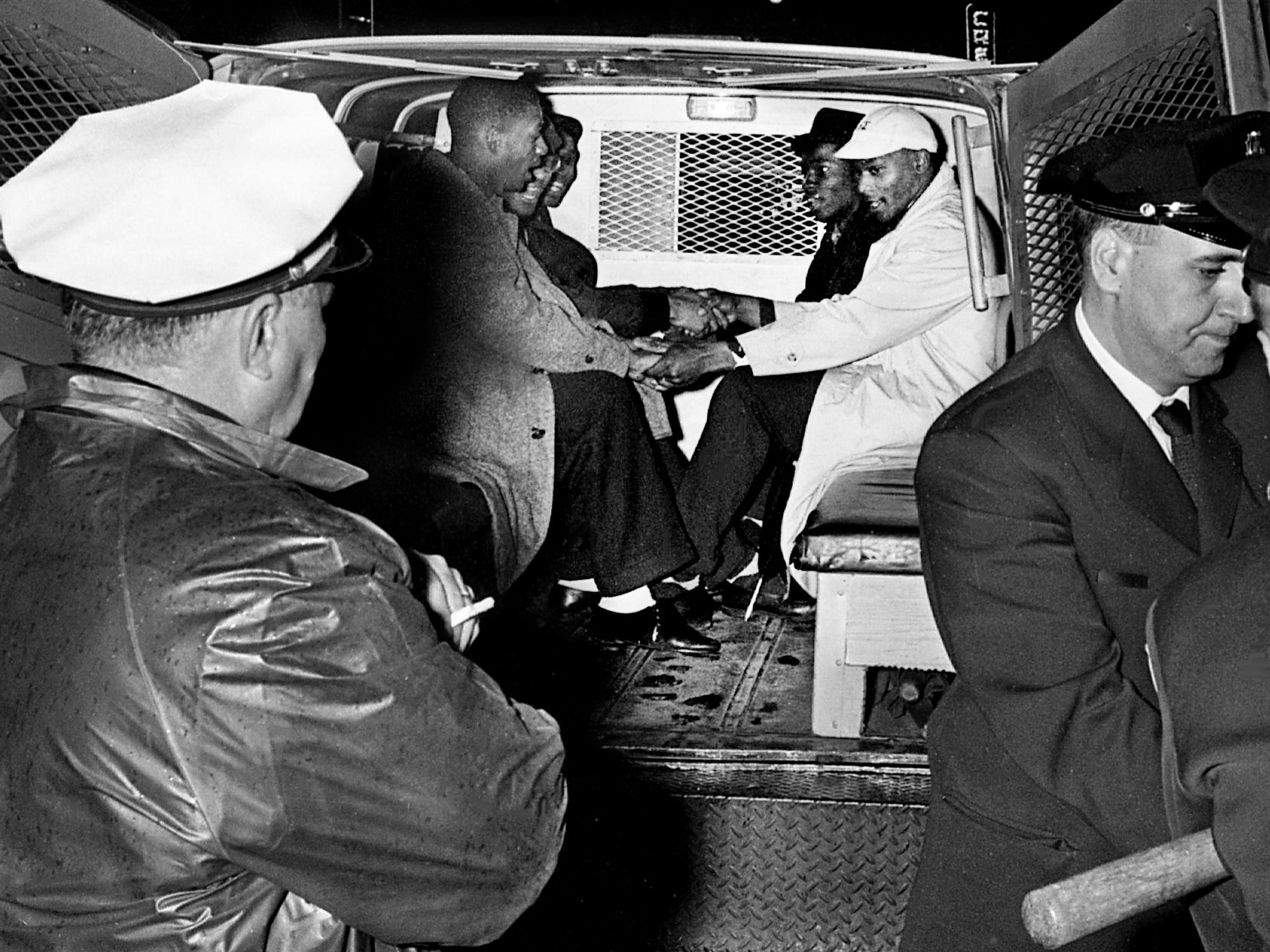 Black college students, including Lester McKinnie, right, greet one another after being put into a Nashville police wagon in front of the Tennessee Theater. The demonstrators allegedly blocked a fire exit and refused to move when ordered to do so by a city fire inspector Feb. 20, 1961. Twenty-eight demonstrators were arrested and charged with violating a section of the city code relating to fire exits.
