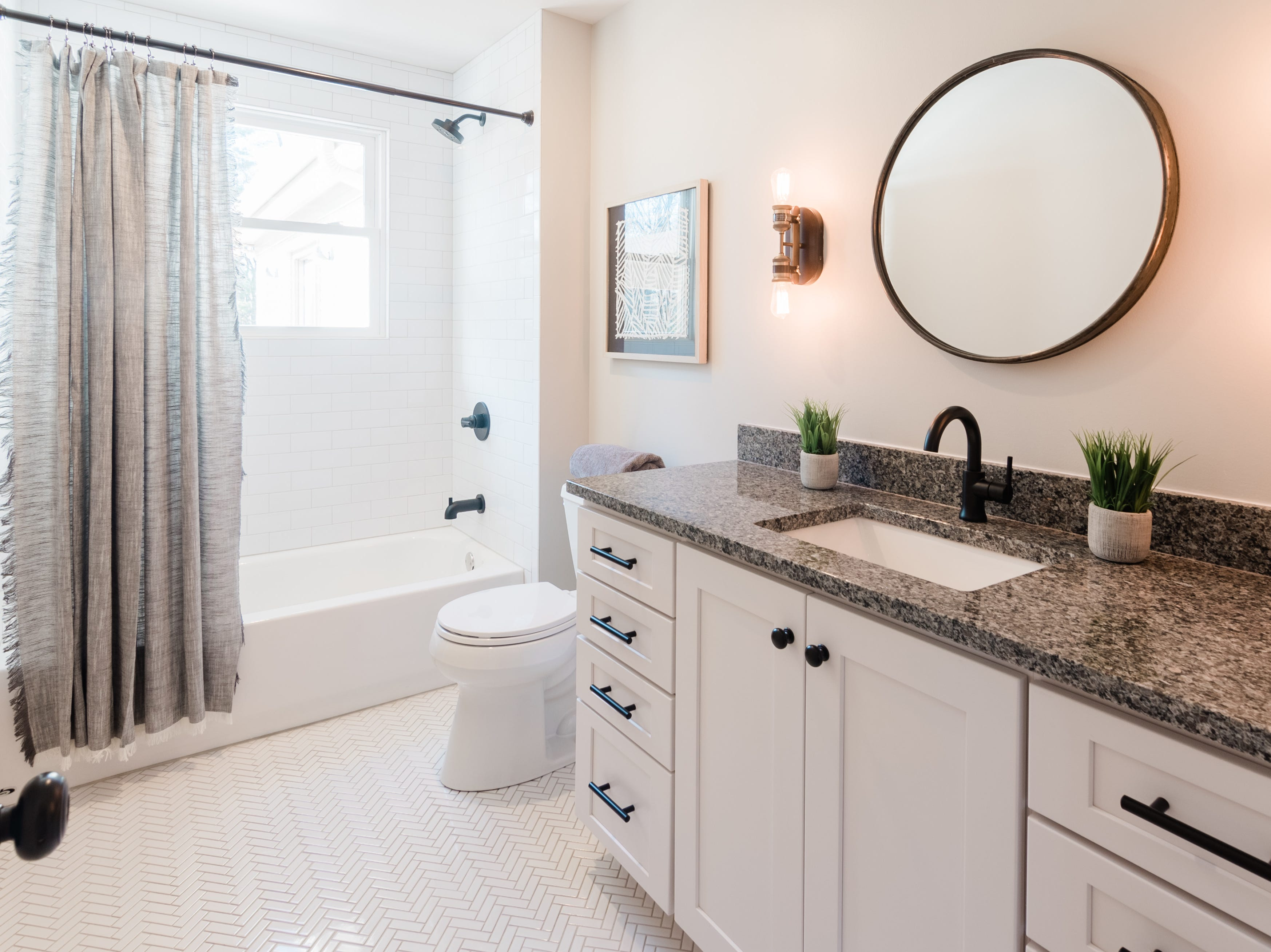 AFTER: This bathroom in the home at 405 Oakvale was remodeled to have more space as well as modern touches such as Chevron subway tiles on the floor and Craftsman-style cabinets.