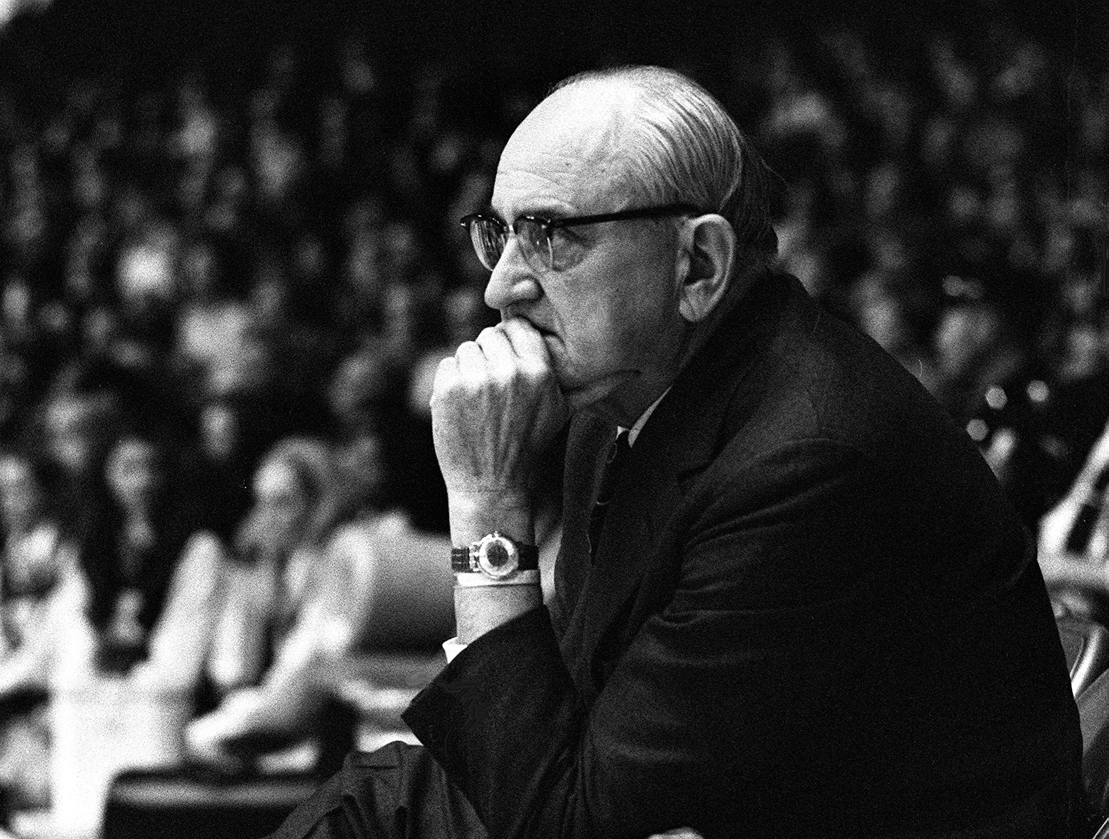 Kentucky ailing head coach Adolph Rupp, with his bad foot on a chair, watches his assistant coach Joe B. Hall lead the team against Vanderbilt Feb. 27, 1971.