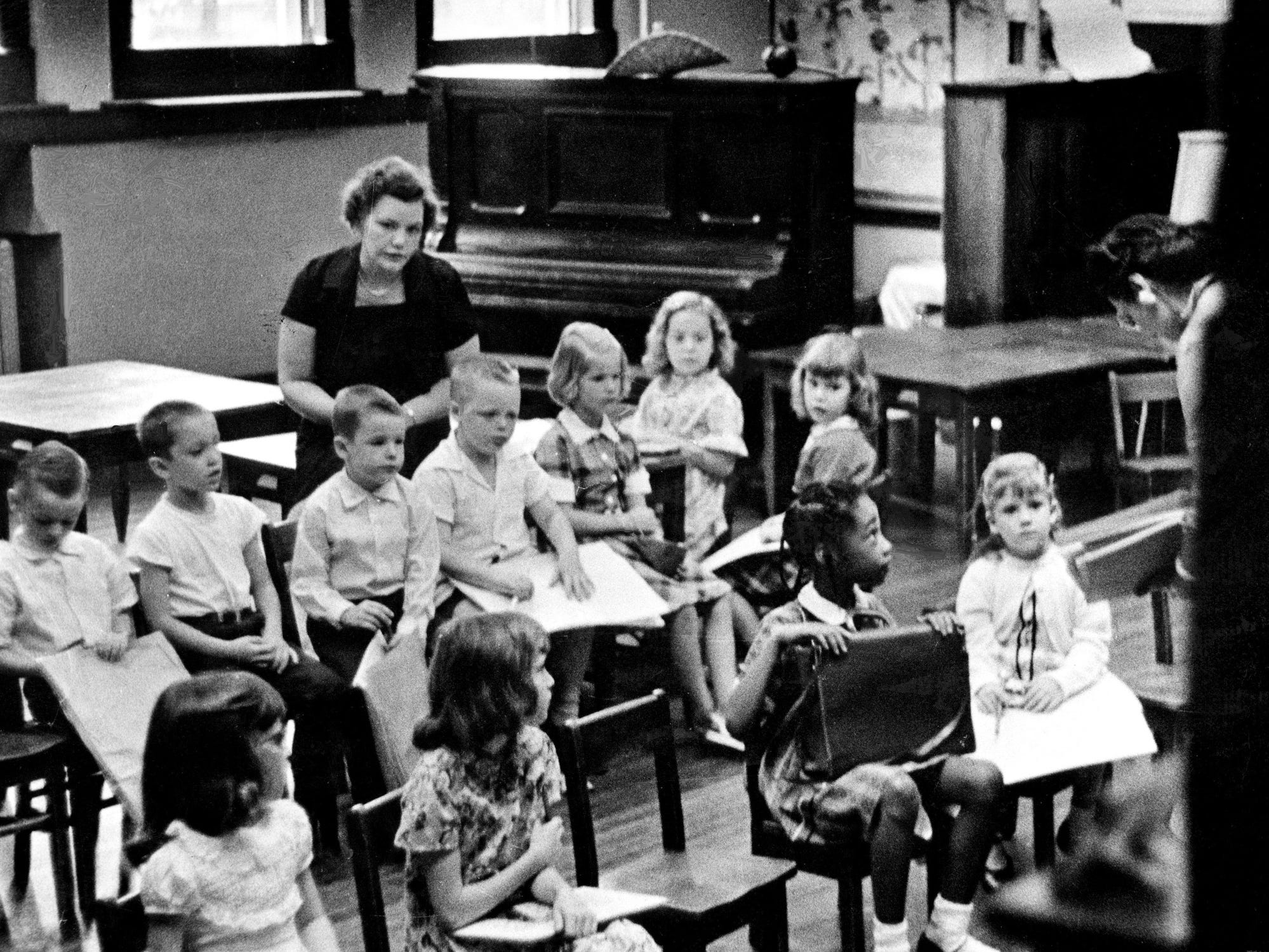 First-graders sit quietly in a classroom at Glenn Elementary School as the school begins its term Sept. 9, 1957. Holding a school satchel is 6-year-old Jacquelyn Faye Griffith, one of two black children integrated into the school.