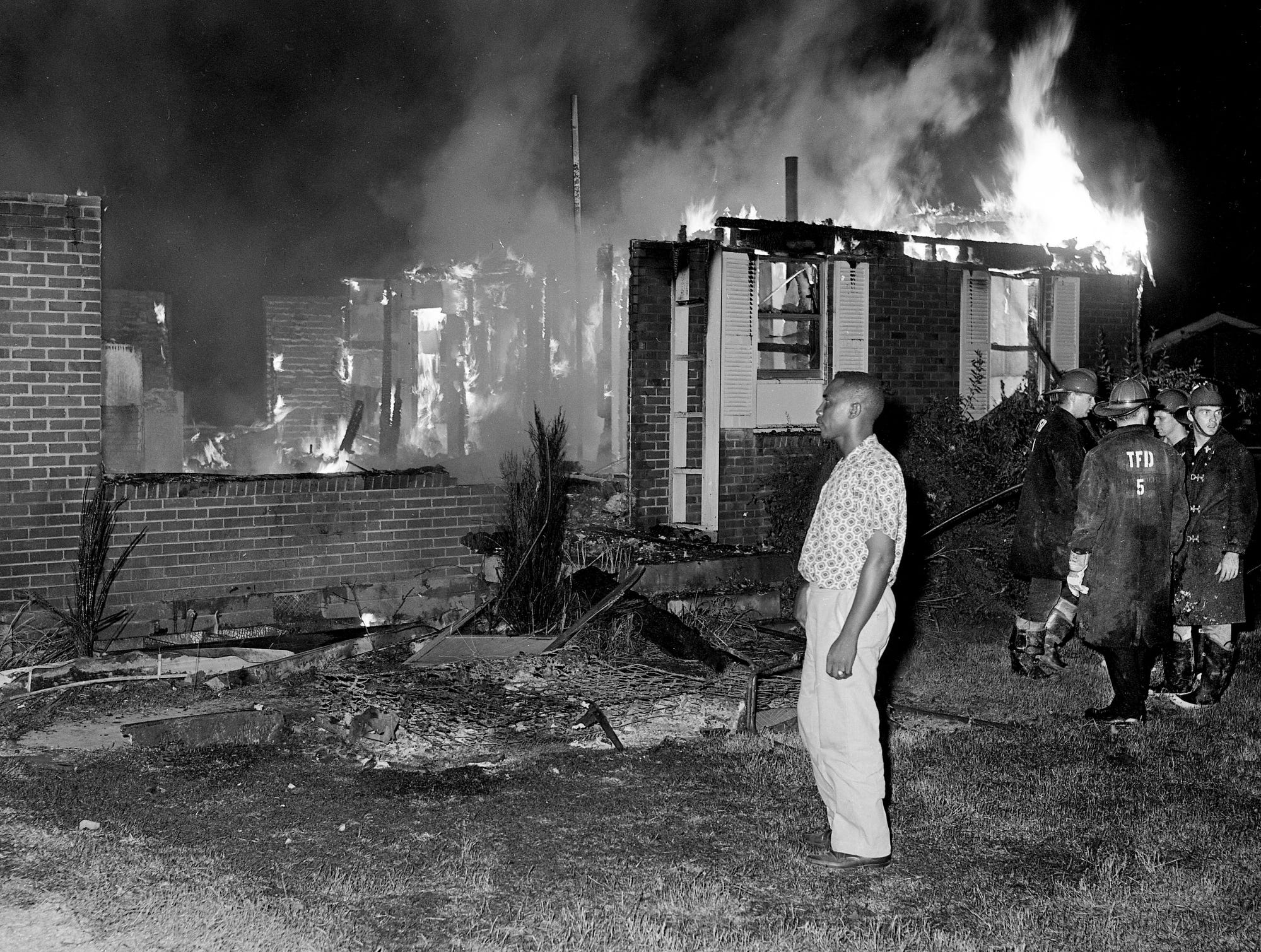 "Tusculum firefighters, right, stand by to protect homes on either side of the burning home of the Rev. Cephus C. Coleman, center, a black minister. His home, which is in a predominantly white neighborhood, was destroyed by the third blaze to break out the night of Aug. 7, 1962. The Davidson County sheriff's chief investigator later said ""arson is definitely the cause"" of the fire."