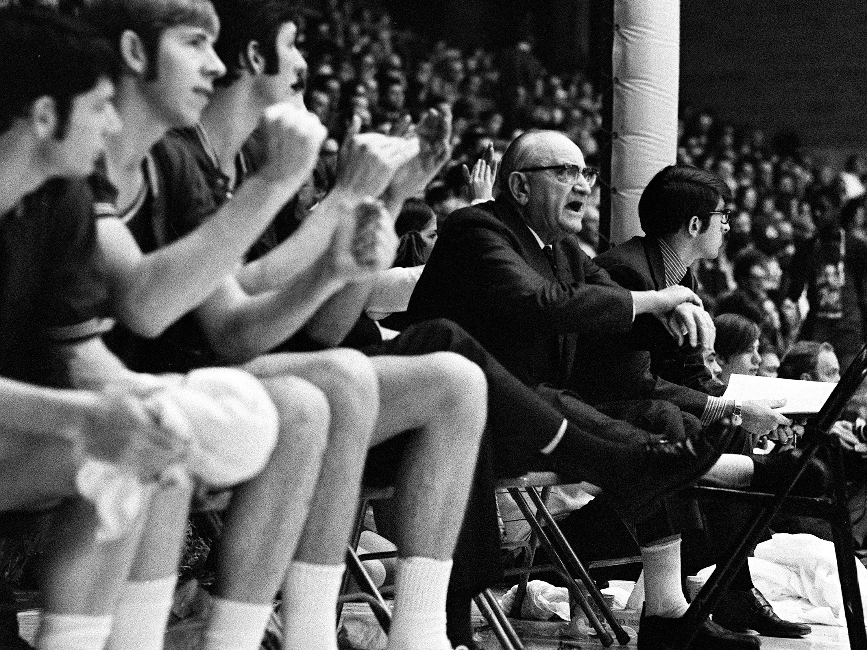 Kentucky ailing head coach Adolph Rupp, second from right, with his bad foot on a chair, watch his assistant coach Joe B. Hall lead the team against Vanderbilt Feb. 27, 1971. Rupp left a Lexington's hospital for a flight to Nashville accompanied by his physician. The Wildcats tagged the Commodores with its most lopsided loss in seven years, 119-90 before 15,581 fans at Memorial Gym.
