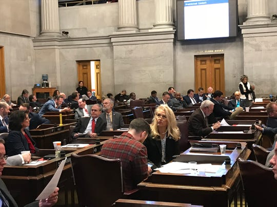 Rep. Robin Smith, center, looks at an overhead presentation while Rep. Michael Curcio, wearing a red jacket uses phone, during a sexual harassment training as for the Tennessee House of Representatives on Jan. 10, 2019.
