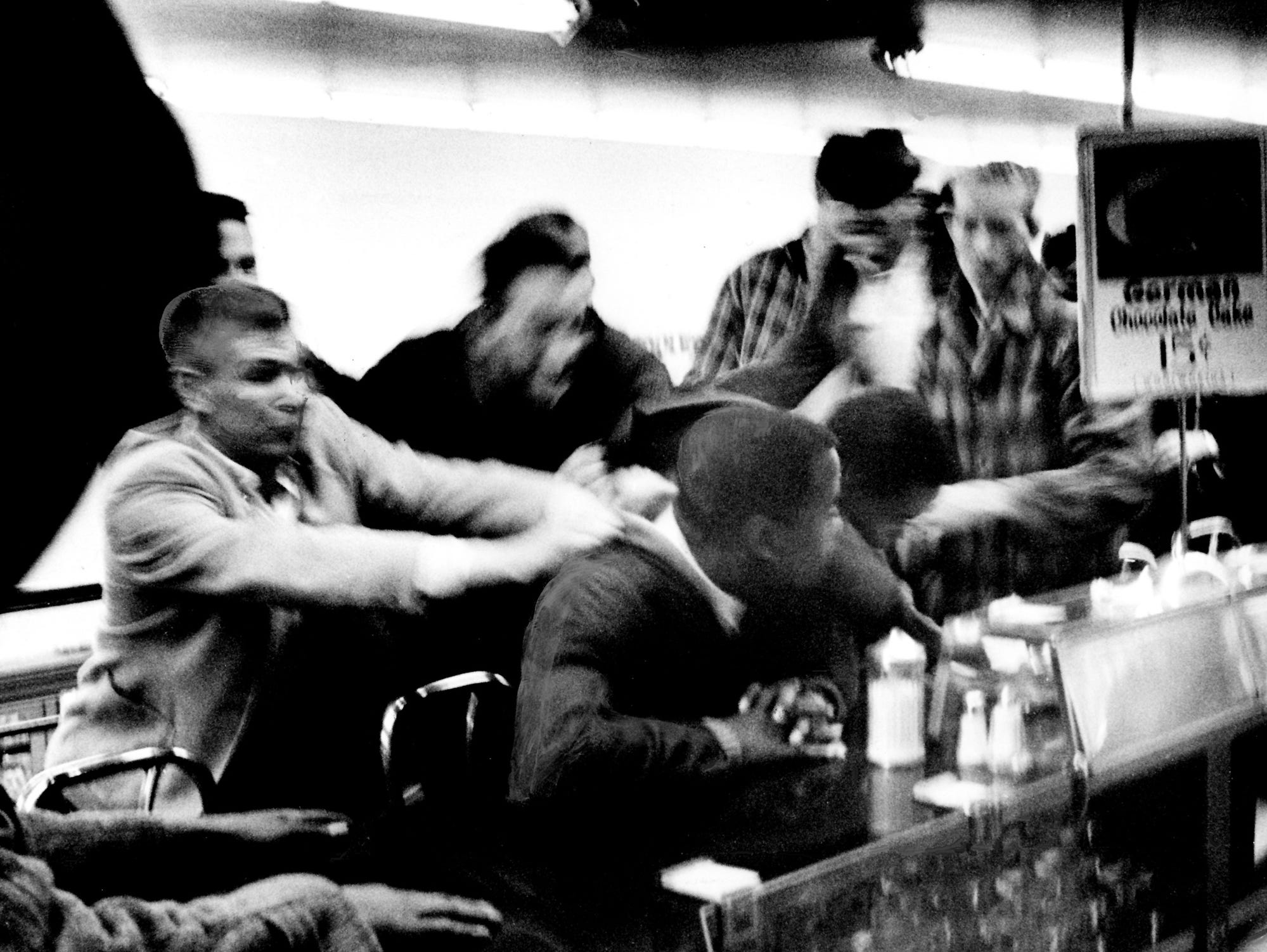 Several white men, left, attempt to drag black students from the lunch counter where they staged a sit-down against segregation in the downtown Woolworth's store Feb. 27, 1960. Police marched into three variety stores and arrested 73 students, most of them seeking lunch counter integration.