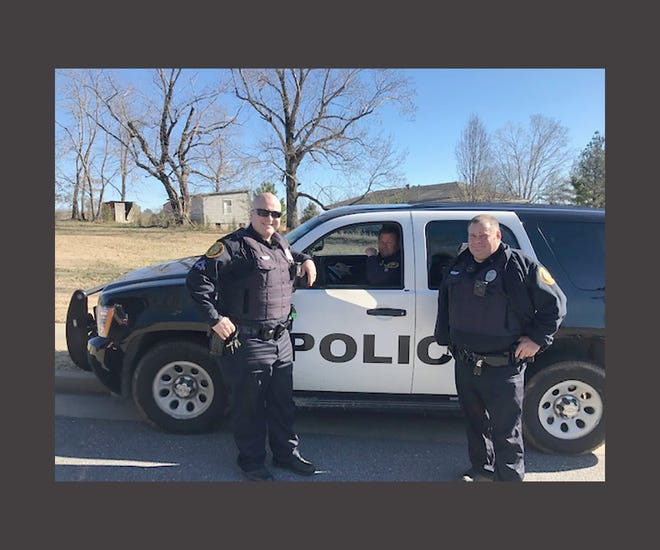 Three Fairview police officers (l-r) Richard Ross, Ronnie Conner and David Howell assist in rescue three stray dogs roaming through a busy Fairview commercial area on Jan. 9.