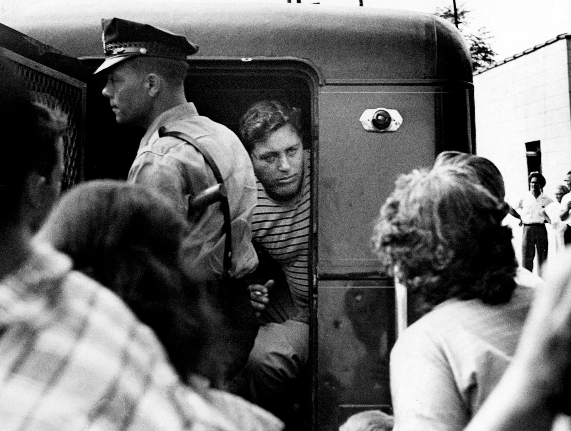 G.H. Akin, center, peers from the back of the paddy wagon before he was taken into city court after his arrest for disorderly conduct Sept. 10, 1957. Nashville police clamped down on segregationist demonstrations by hauling 19 other demonstrators to jail on the second day of school.