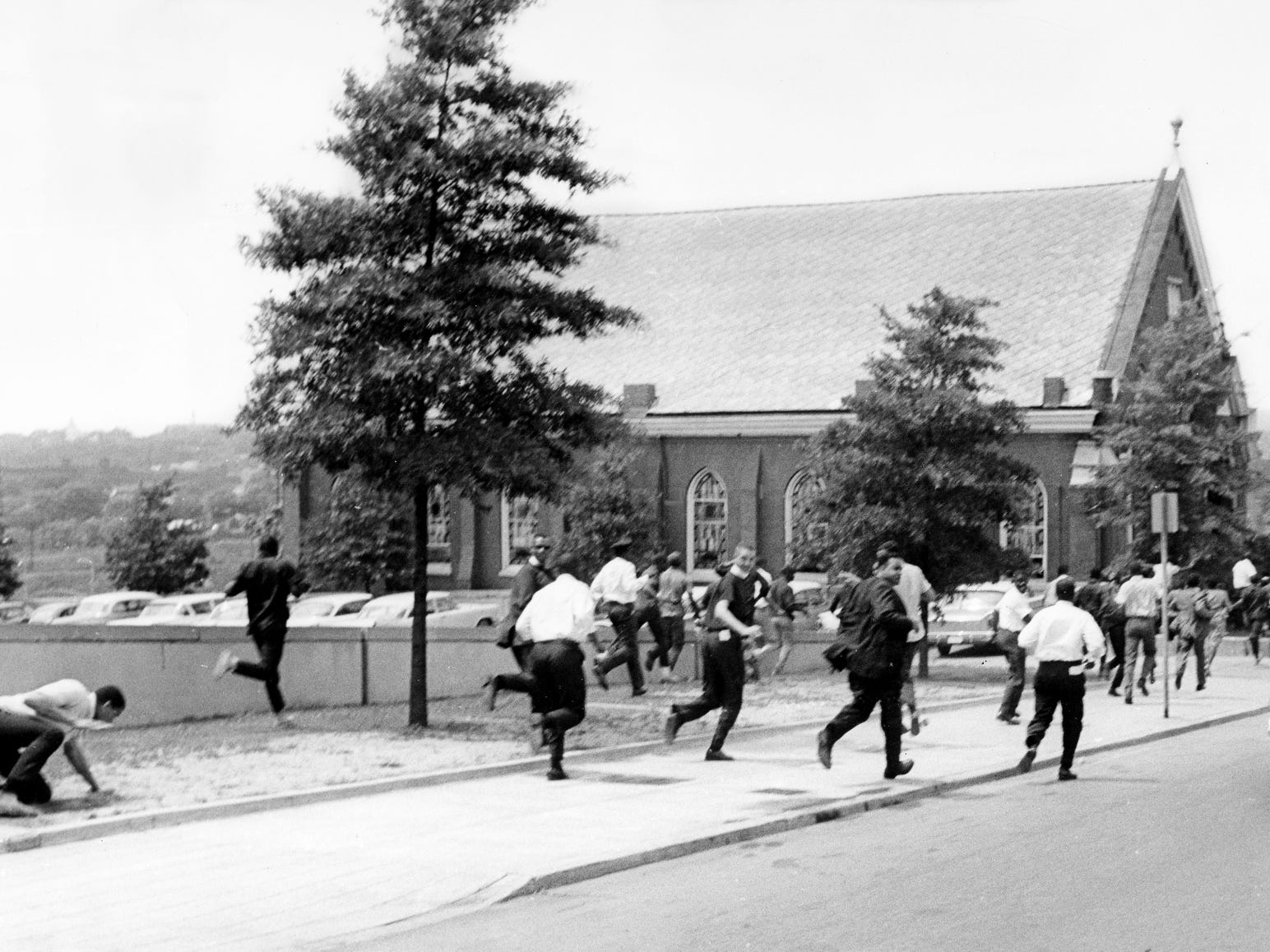 Black demonstrators race back to the safety of First Baptist Church after daylong protest marches downtown May 8, 1963. One of the leaders of the demonstrators, the Rev. J. Metz Rollins, center, guided the protesters back home. After they returned from the final march, a group of about 30 white youths began throwing rocks and soft drink bottles.
