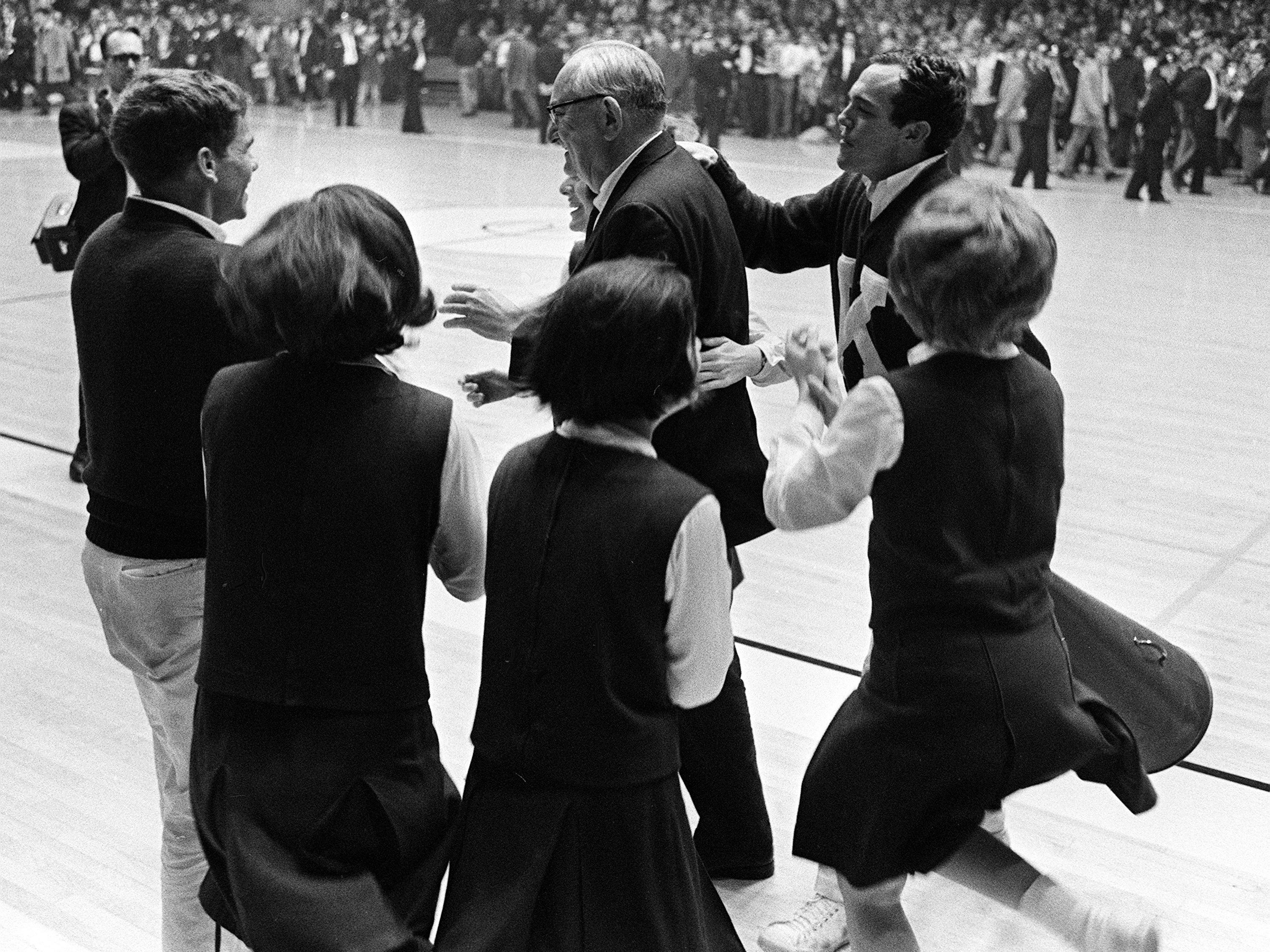 Kentucky head coach Adolph Rupp, center, gets help from the cheerleaders in celebrating their victory over Vanderbilt. The undefeated Wildcats won 105-90 over the Commodores before more than 9,500 fans Feb. 2, 1966.