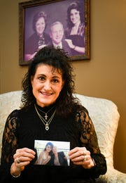 Linda Carol Trotter holds a picture of herself with her biological mother while sitting in front of a portrait of herself with her adoptive parents Jan. 3, 2019, in Franklin.
