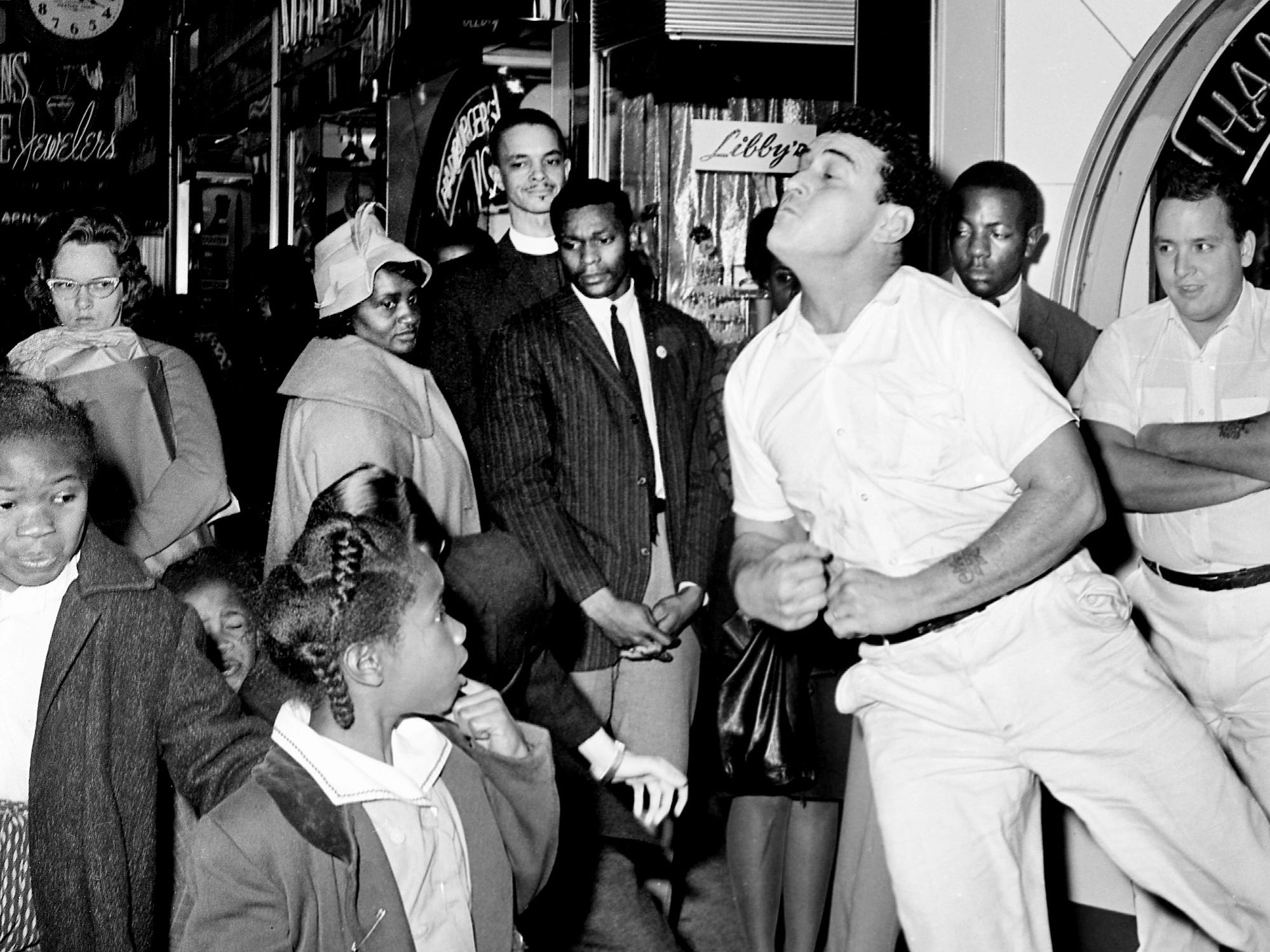 A little girl, left, watches in awe as Jan Emmert, a Fisk University student, lands behind her after he was shoved by Bobby Gene Taylor, a restaurant employee. The hassle came Dec. 1, 1962, during a sit-in attempt at the Herschel's Tic Toc restaurant on Church Street. Looking on are demonstrators Lester McKinnie, center, and the Rev. J. Metz Rollins, behind McKinnie.