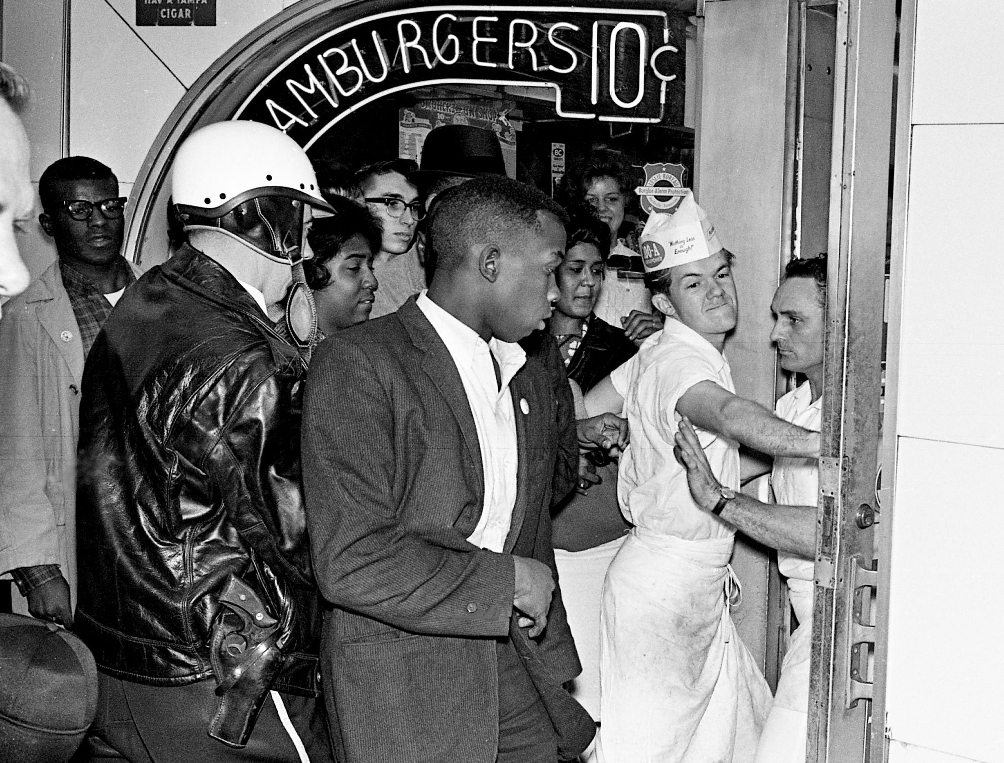 Two employees of Herschel's Tic Toc restaurant, right, form a human barricade to block sit-in demonstrators, including local leader John Lewis, center, from entering the Church Street establishment Nov. 24, 1962. Nashville officers moved in quickly to quell a series of incidents throughout the two-hour sit-ins.