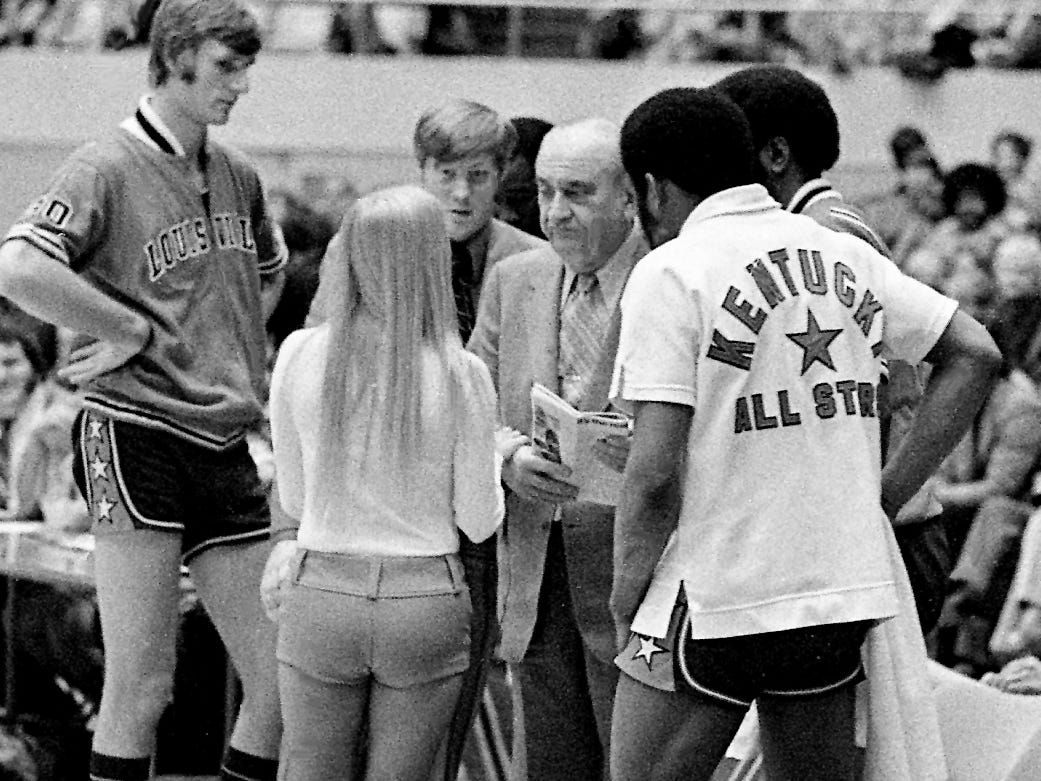 The retiring Kentucky coach Adolph Rupp, center, coaching in the Kentucky-Tennessee All-Star game at Municipal Auditorium, signs an autograph for one of the ball girls before the game April 1, 1972.