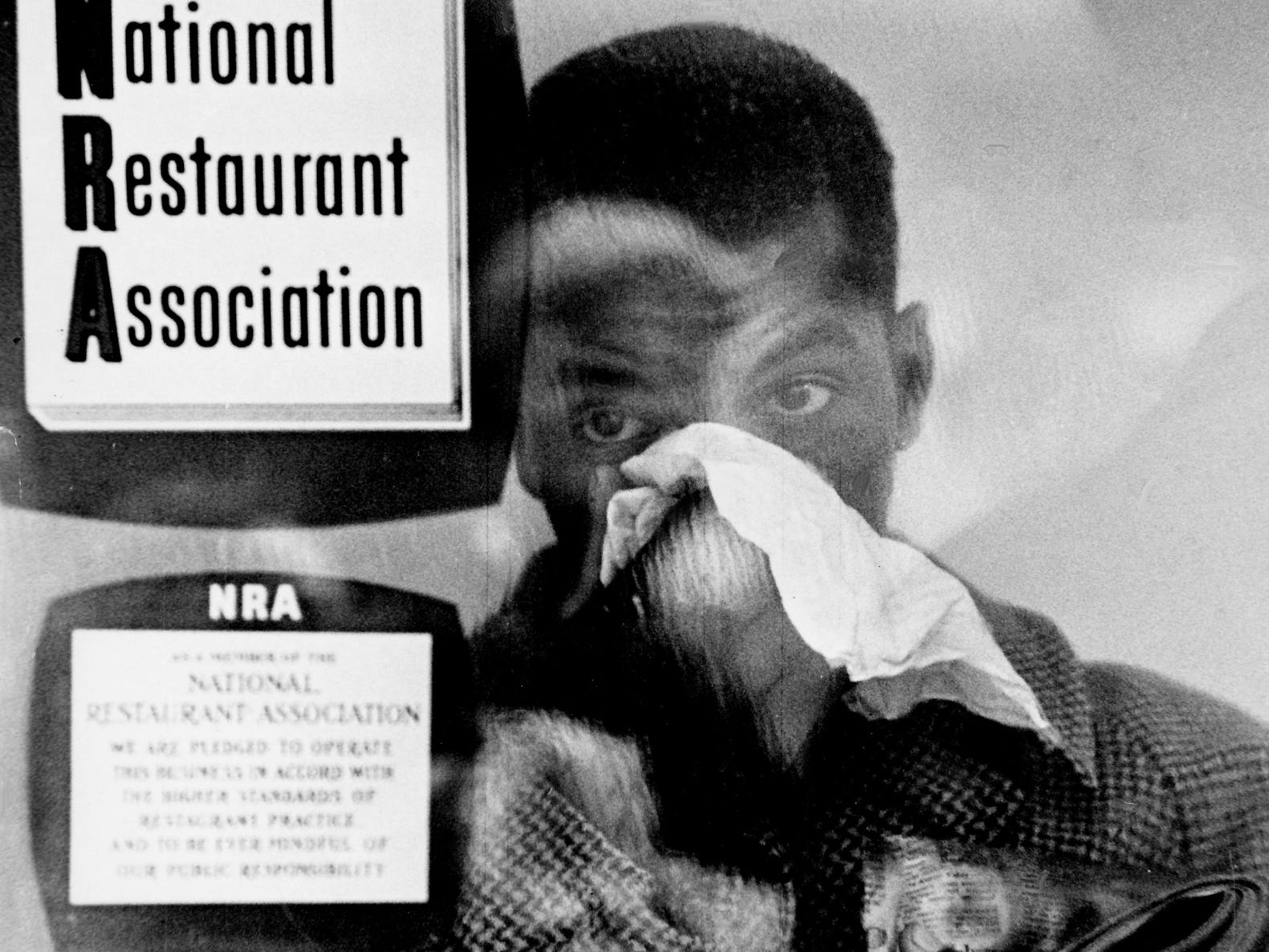 Gasping for breath, John Lewis stands inside the insecticide fume-filled Krystal lunch counter at 204 Fifth Ave. N. in downtown Nashville on Nov. 10, 1960, after the manager turned on a fumigating machine to disrupt Lewis and fellow sit-in demonstrator James Bevel.
