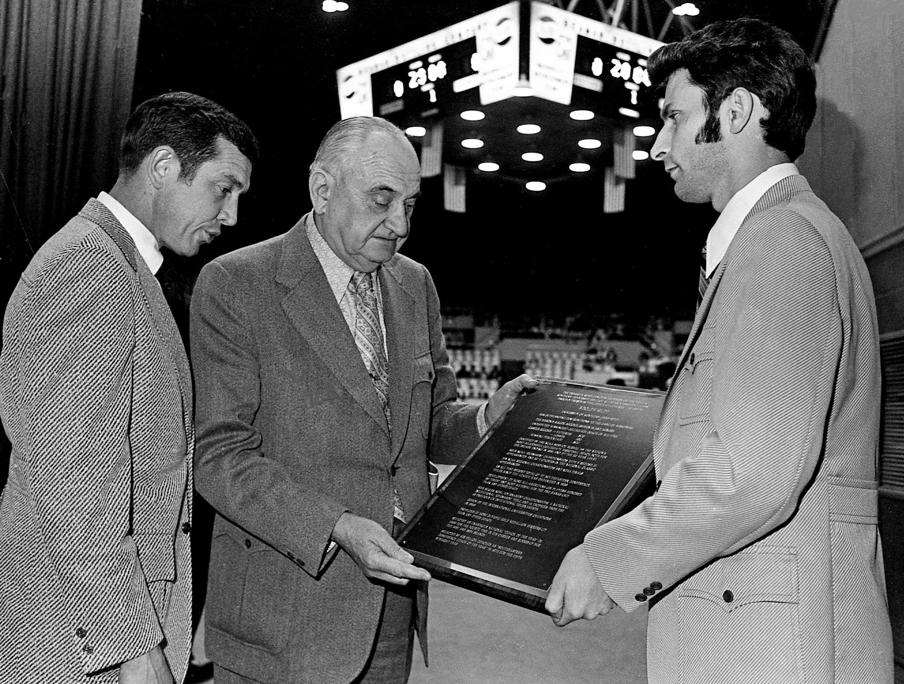 Coach Adolph Rupp, center, examines the plaque presented him before the start of the Kentucky-Tennessee All-Star game April 1, 1972. Looking on at the enumeration of the nation's winning coach are Vanderbilt coach Roy Skinner, left, and Dave Shelton of the sponsoring Franklin Road Jaycees, who presented the award.
