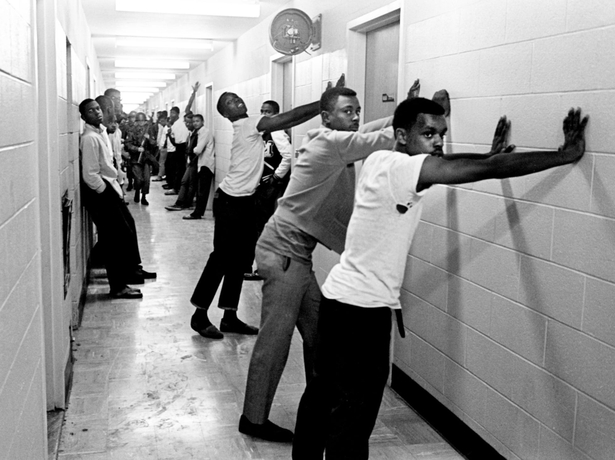 Tennessee A&I State University students line up in the hallway of their campus dorm as National Guardsmen and Metro police officers search them and their rooms in the early hours of April 6, 1968. They searched three campus dorms after police officers had been pinned behind a wall by gunfire.