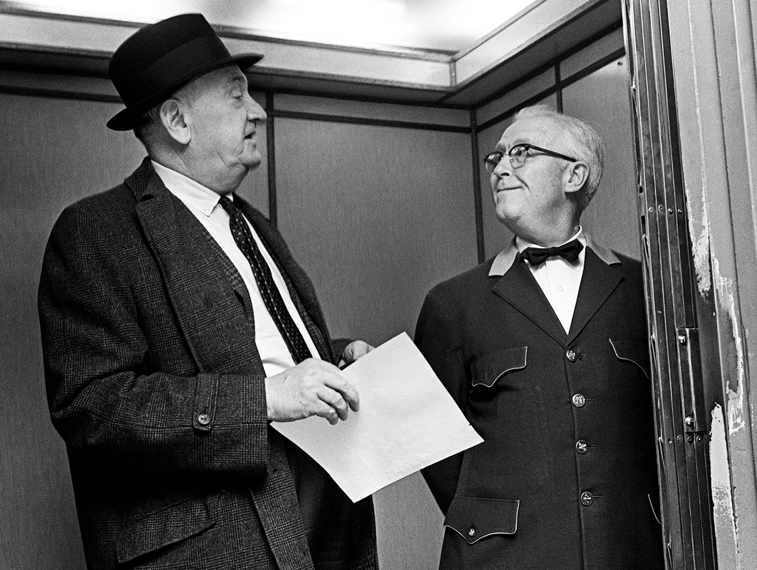 Kentucky head coach Adolph Rupp, left, found an old friend waiting as he got to the elevator to go to his room at the Noel Hotel in Nashville Feb. 1, 1966. Ernest Mathis, right, has been hauling the veteran Wildcat mentor for years.