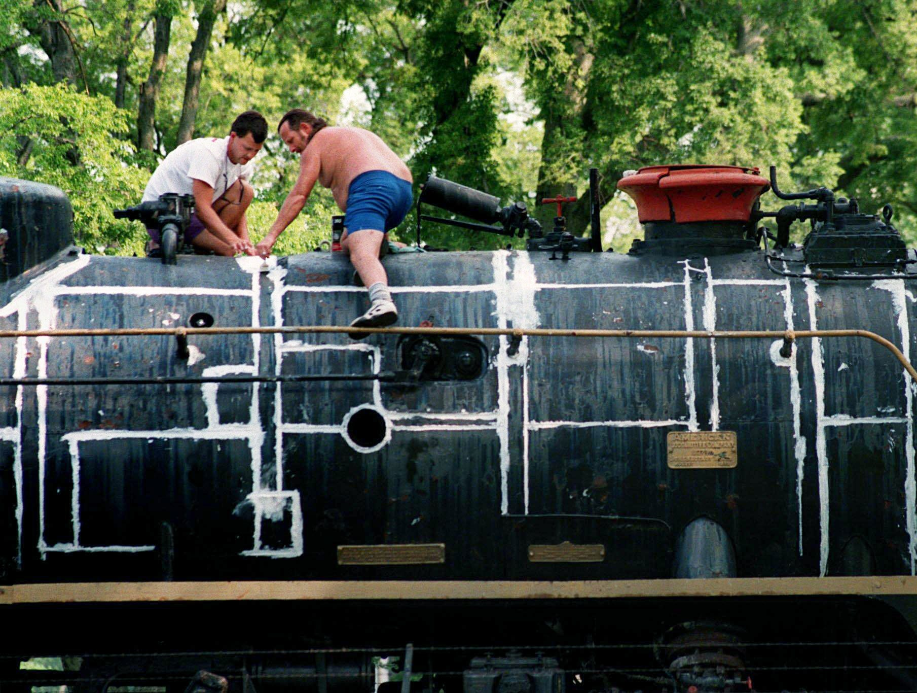 Joe White, right, and his son Joe White IV, seal the seams of the Nashville, Chattanooga and St.Louis steam locomotive 576 in Centennial Park July 23, 1997. Asbestos was removed from around the boiler before White and his son seal the engine before painting. The steam engine was presented to Nashville in 1953. The engine, built in 1942, was used extensively during WW II to transport personnel and war supplies.