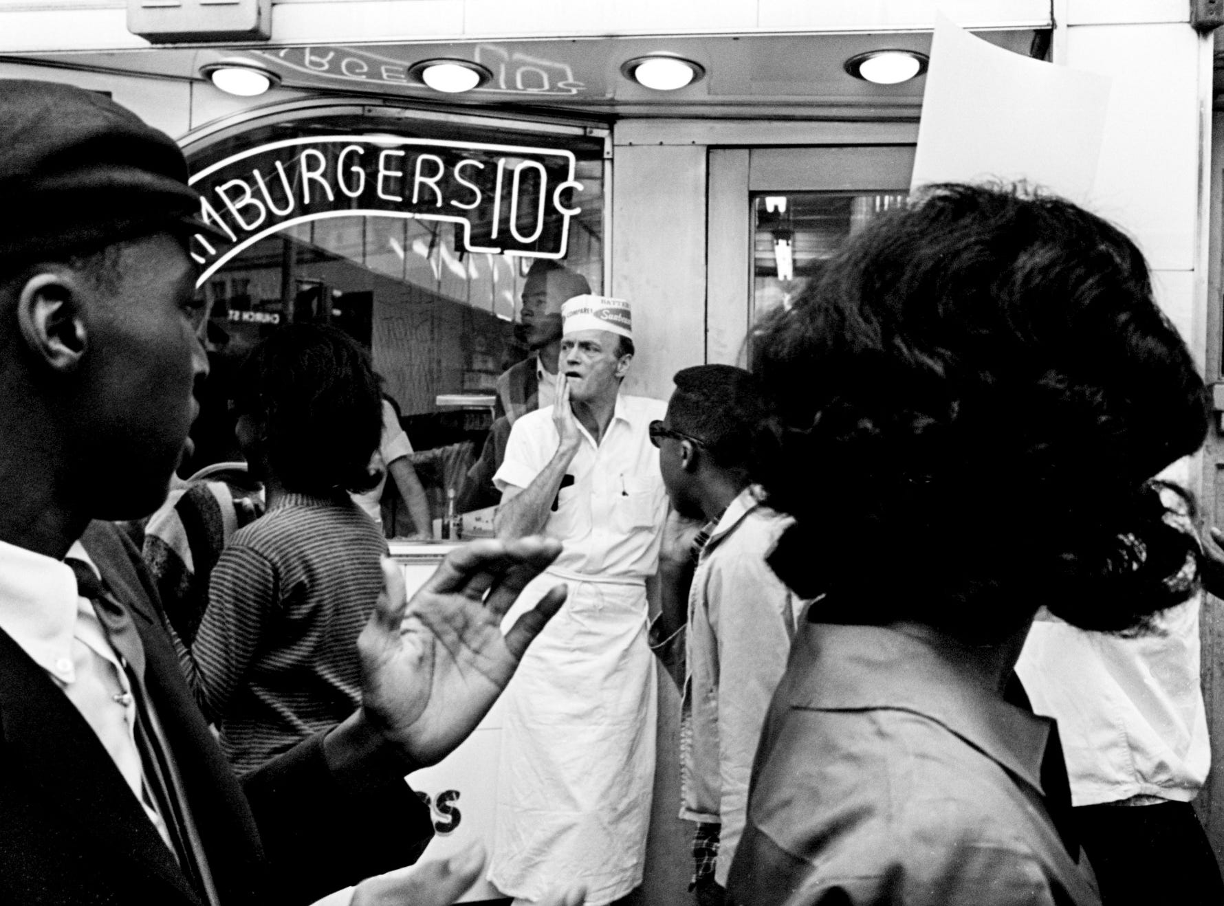 A Tic Toc Restaurant employee keeps an eye on one of the five groups of 25 demonstrators parading in front of the downtown store May 1, 1964. They marched in front of six segregated restaurants for two hours. Two of the marchers, John Lewis and Lewis Miller, were slightly injured during a scuffle in front of the store.