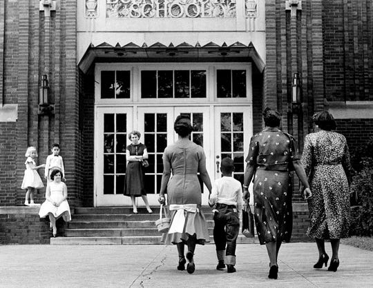 Erroll Groves, second from left, with his mother, Iridella Groves, left, and other family members walk up to the doors of Buena Vista School on the first day of school Sept. 9, 1957. Fifteen black first-graders entered schools and desegregation was established in Nashville.