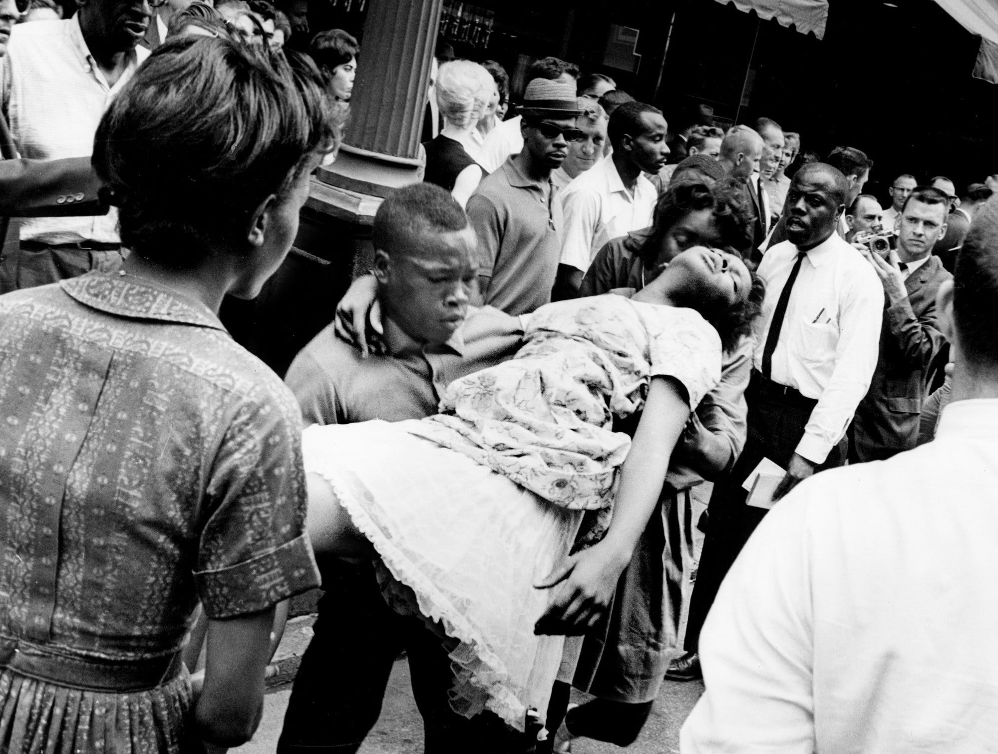 A black youth picks up Ewingella Bigham, 15, who was unconscious in the street, shortly after she was injured during a near-riot between white youths and black demonstrators May 10, 1963. Her sister, left, said the girl was struck with a patrolman's billy stick. She was taken to Hubbard Hospital.