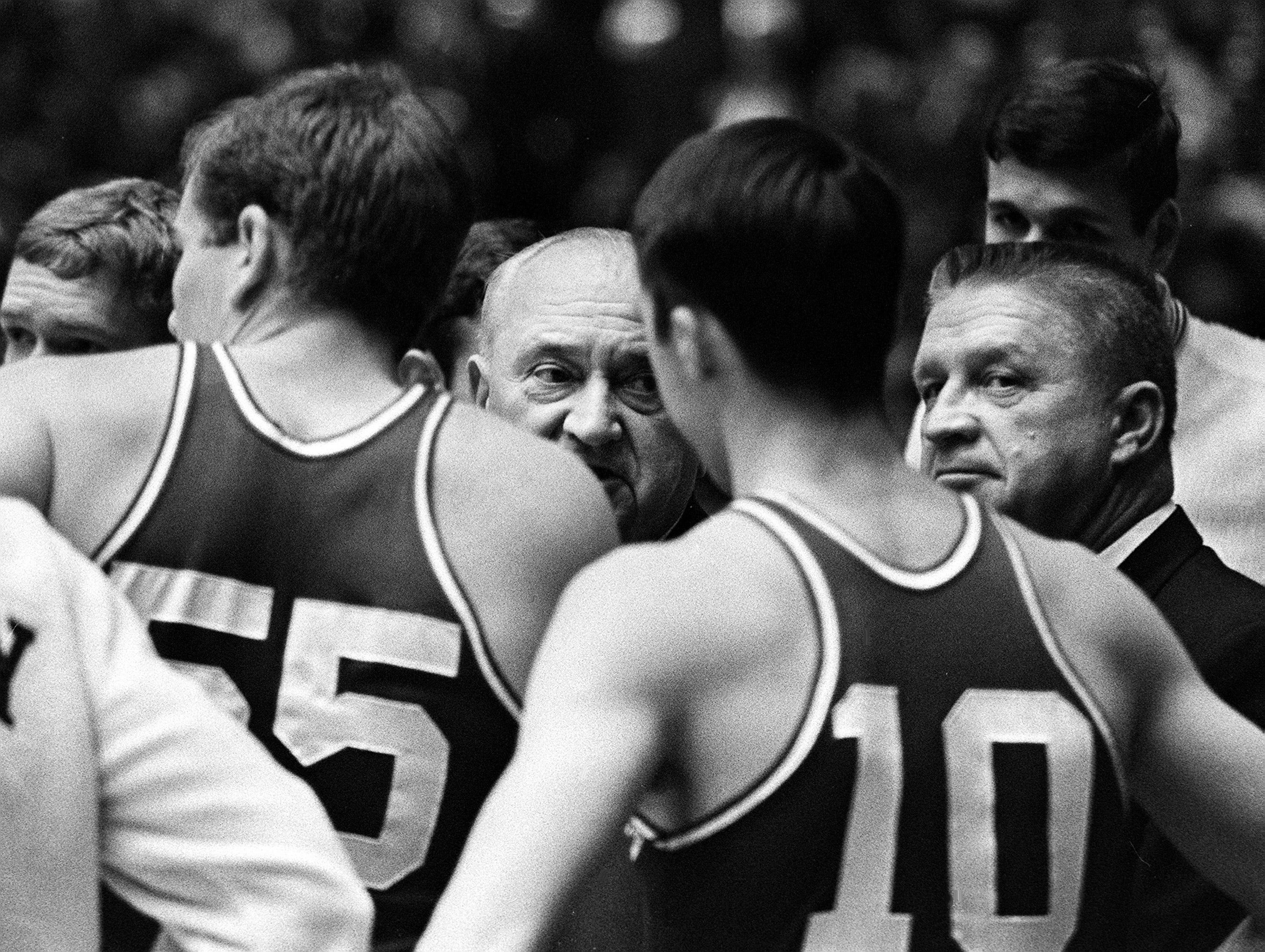 Kentucky head coach Adolph Rupp, center, and assistant coach Harry Lancaster, right, talk with his team during their game at Vanderbilt. The undefeated Wildcats won 105-90 over the Commodores before more than 9,500 fans in Memorial Gym Feb. 2, 1966.
