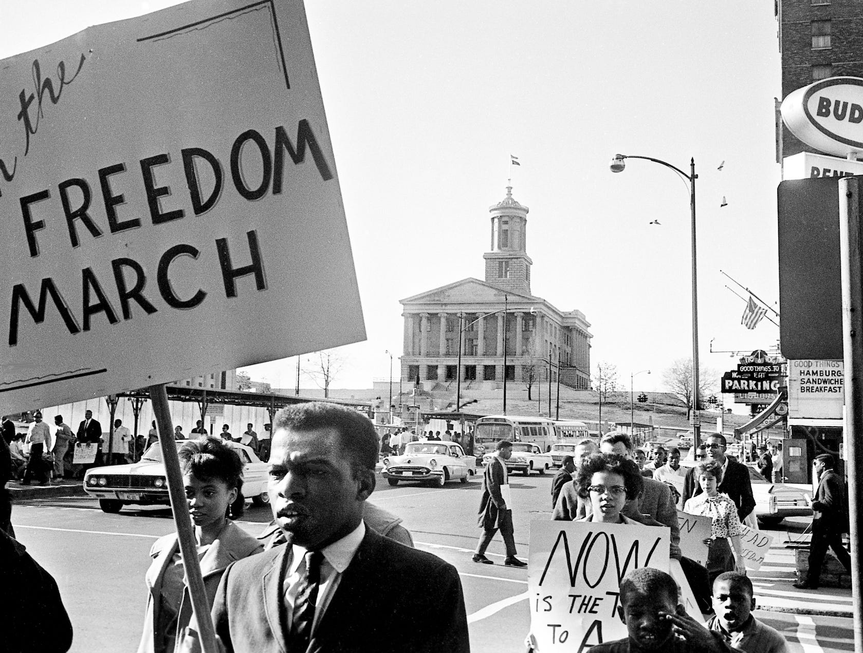 "Demonstrators March 23, 1963, to protest racial discrimination in Nashville. In the foreground at left, with the ""Freedom March"" sign, is John Lewis, chairman of the Student Central Committee of the Nashville Christian Leadership Council, sponsors of the movement."