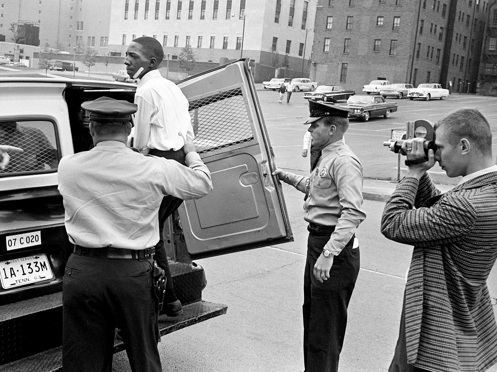 Louis Miller, 16, who was charged with throwing a brick that broke a car windshield, is put into the paddy wagon May 11, 1963, at First Baptist Church. Miller will be on his way to juvenile detention. City photographer Milton McClurkan is at right.
