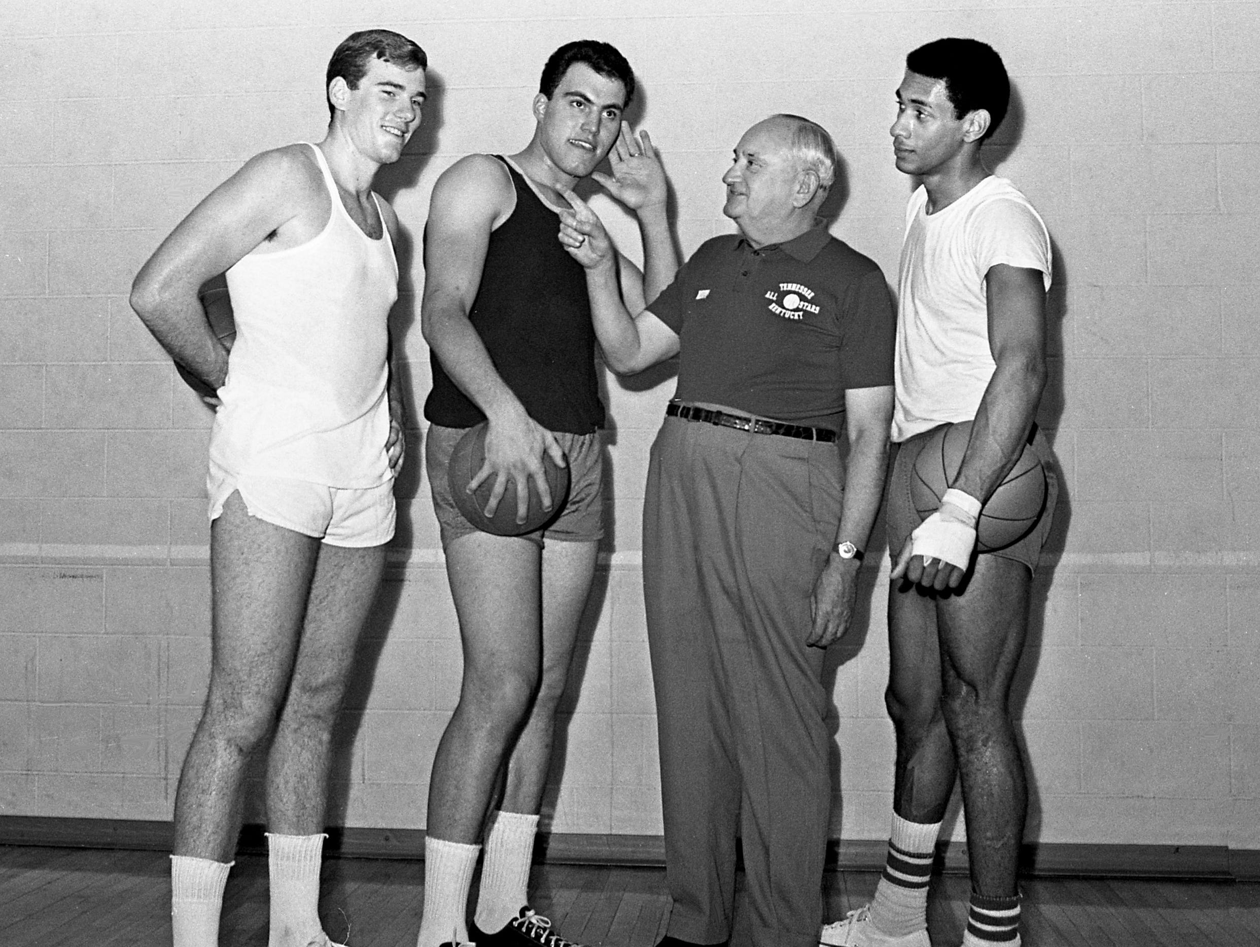 """Now you're coming through loud and clear,"" Dick Cunningham, second from left, of Murray State appears to be thinking as he cups his ear to hear what Kentucky famed coach Adolph Rupp has to say during practice April 12, 1968. Looking on are Thad Jaracz, left, of Kentucky and Greg Smith, right, of Western Kentucky as the Kentucky senior college stars get ready to play the Tennessee senior All-Star team the next day at Memorial Gym."