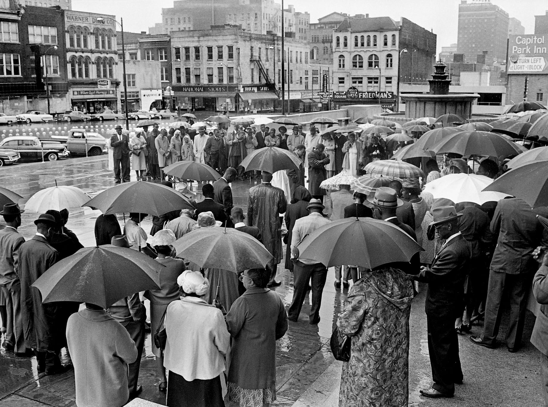 "Black church leaders and other demonstrators huddle under umbrellas as they participate in a ""prayer vigil"" at the Metro Courthouse on April 28, 1963. The group stood for an hour in the rain to petition local government leaders ""to provide justice and equality for all Nashville citizens."""