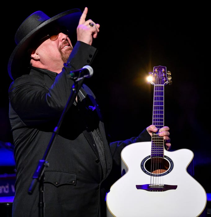 Eddie Montgomery brings Troy Gentry's guitar to the stage during the C'Ya On The Flipside Benefit Concert at the Grand Ole Opry House in Nashville, Tenn., Wednesday, Jan. 9, 2019.