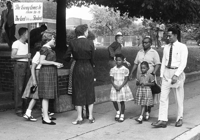 First-grader Patricia Guthrie, left, with her mother, Mrs. Horace Guthrie, and first-grader Ethel Mai Carr, with her father, Virgil, walk past a crowd protesting their integration at Buena Vista School on Sept. 9, 1957.