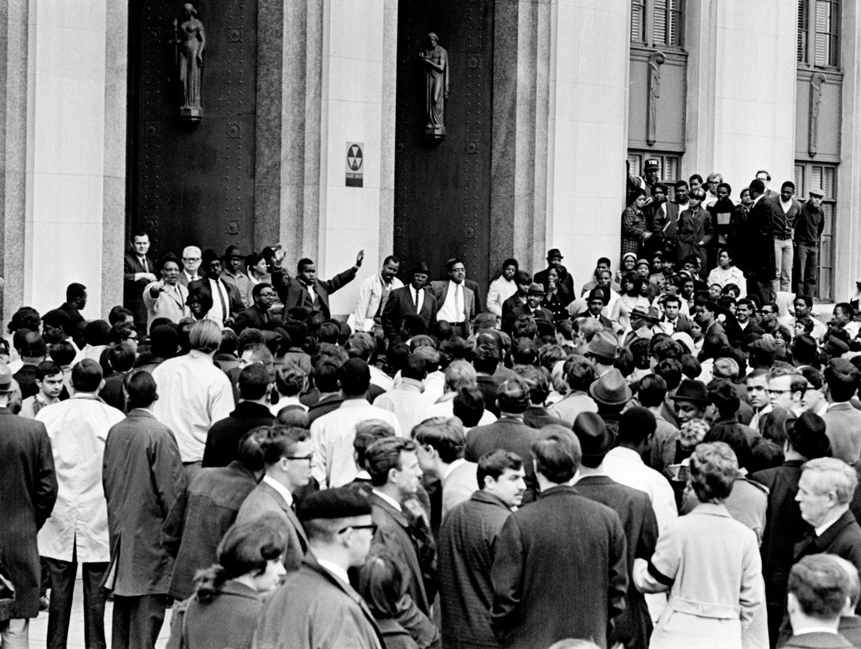"Outside the city hall and courthouse building, a black leader raises his hands for quiet as a crowd of 1,000 chants, ""We want Briley."" After many in the crowd attended memorial services for the Rev. Martin Luther King Jr., they gathered for Mayor Beverly Briley on April 5, 1968. He met with black leaders in his office but declined to address the crowd outside."