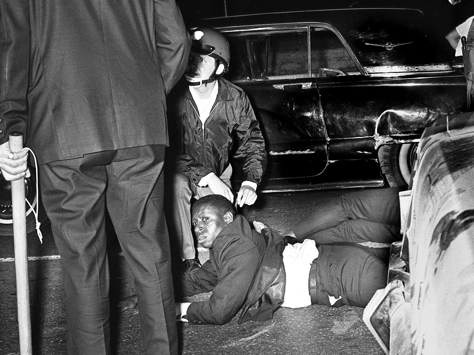 Metro police officers and occupants of a car duck bullets, which were fired by rioters at the Tennessee State University campus April 9, 1967. Rock throwing escalated to gunfire as violence erupted, sending mobs and riot police swarming through North Nashville's black community.