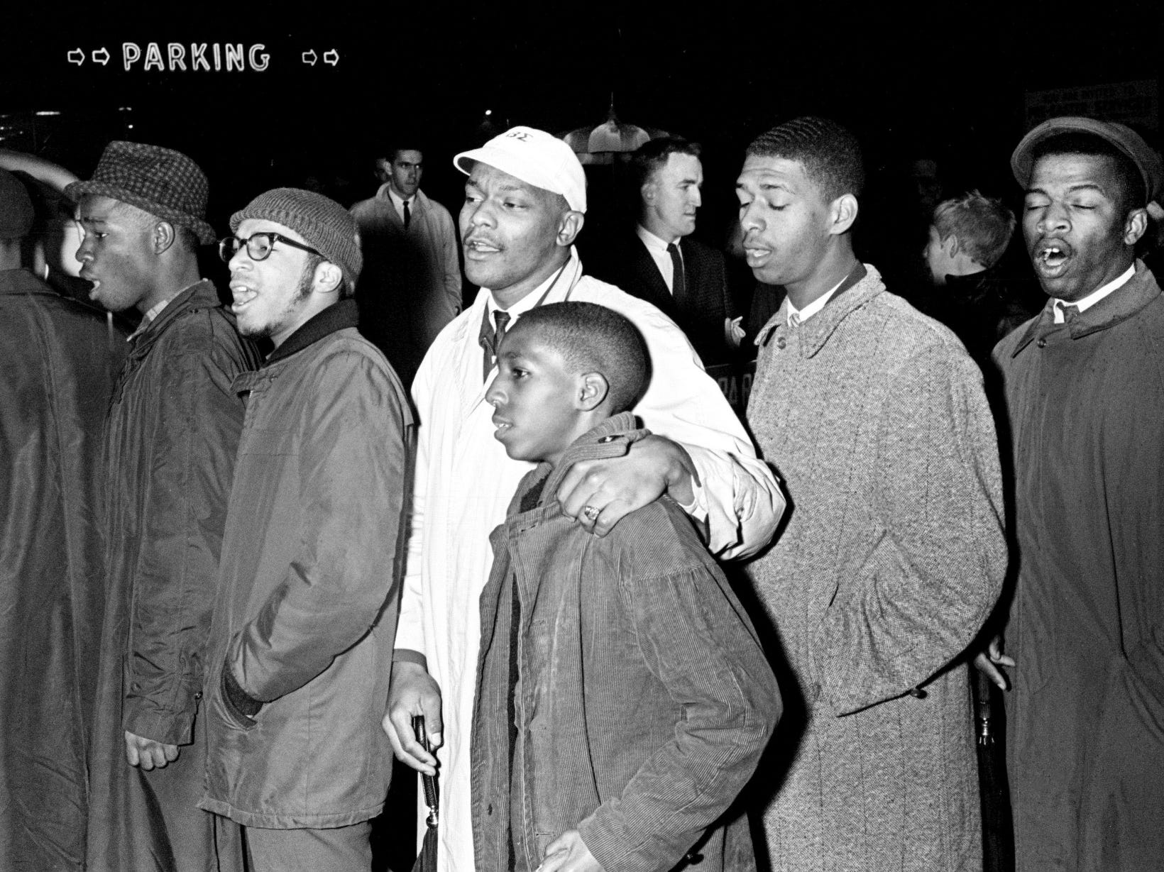 Black students begin to sing as they wait to load up in Nashville police wagons after being arrested for blocking a fire exit at the Tennessee Theater downtown Feb. 20, 1961. In the group are Lester McKinnie, center in white cap, and John Lewis, right.