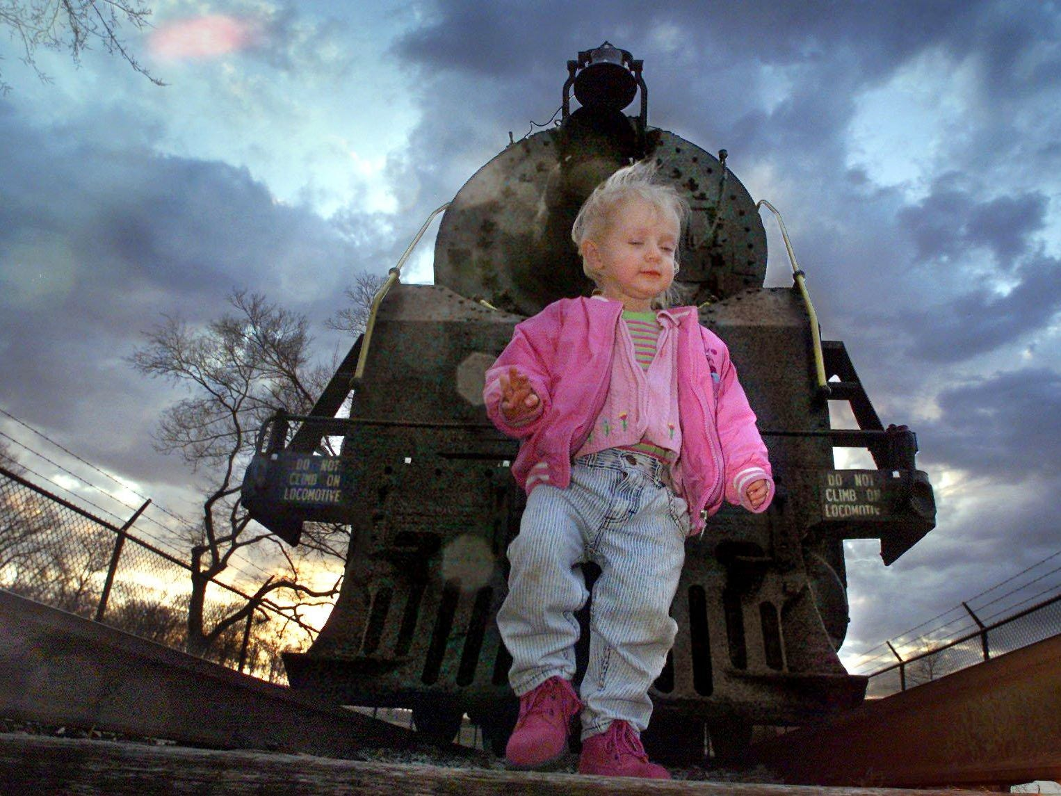 Haley Stevens, 2, plays in Centennial Park Feb. 8, 2001 in front of the steam locomotive that's been a long-time favorite in the park for decades.