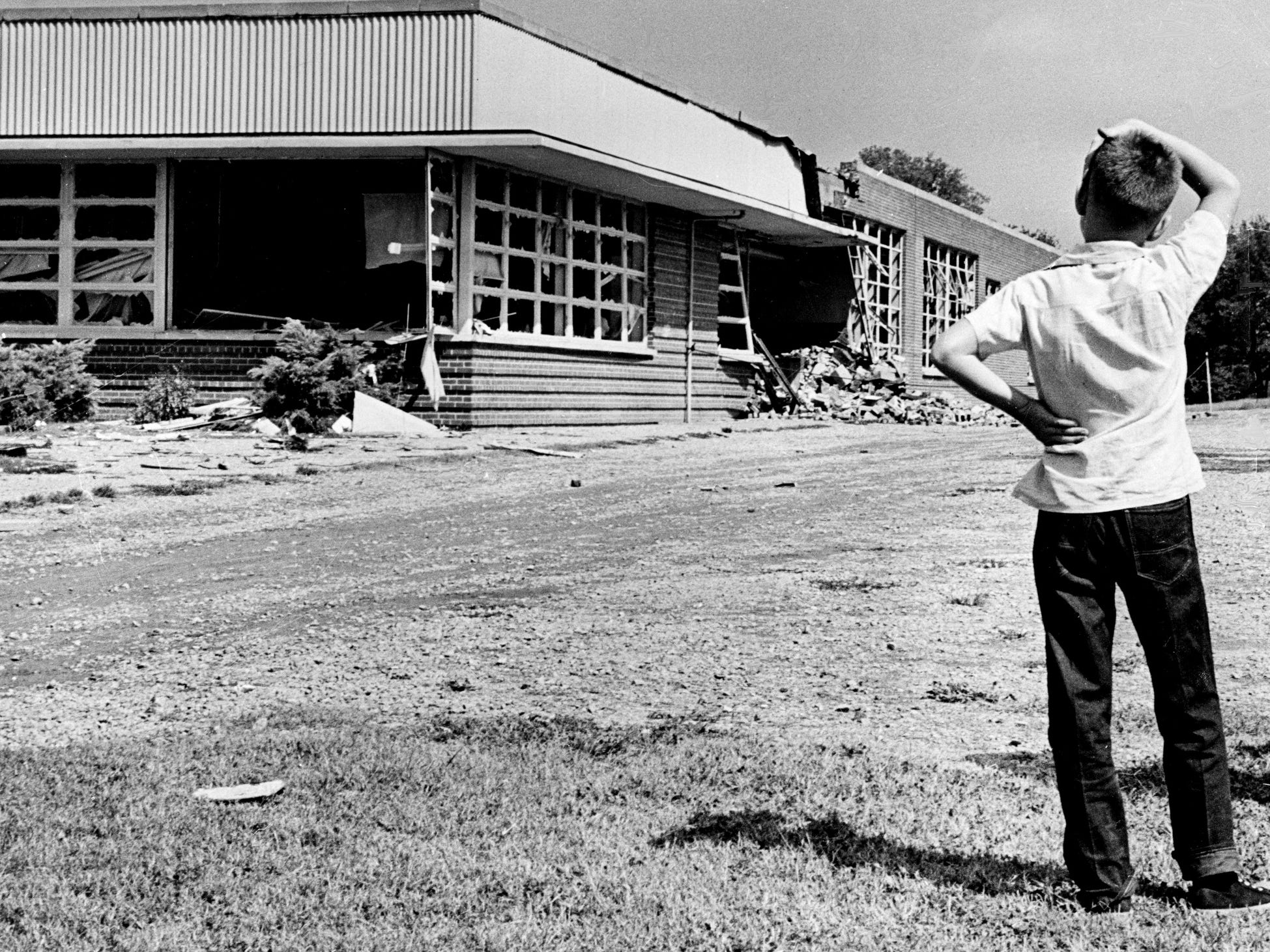 A boy surveys the damage done by dynamite to Hattie Cotton School, where 390 first- through sixth-grade students normally attend, on Sept. 10, 1957.