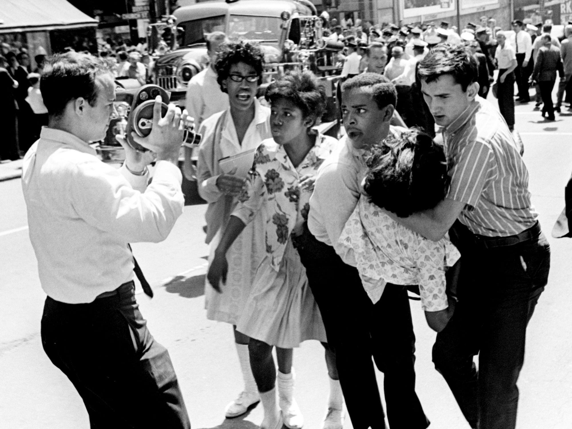 Fellow civil rights demonstrators carry an injured marcher after violence erupted when club-swinging police officers surged through the marchers on Church Street on April 28, 1964.