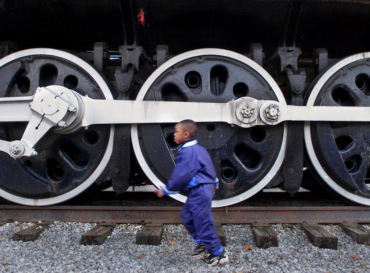 Parrian Clark, 5, plays in Centennial Park Feb. 8, 2001 in front of the steam locomotive that's been a long-time favorite in the park for decades.