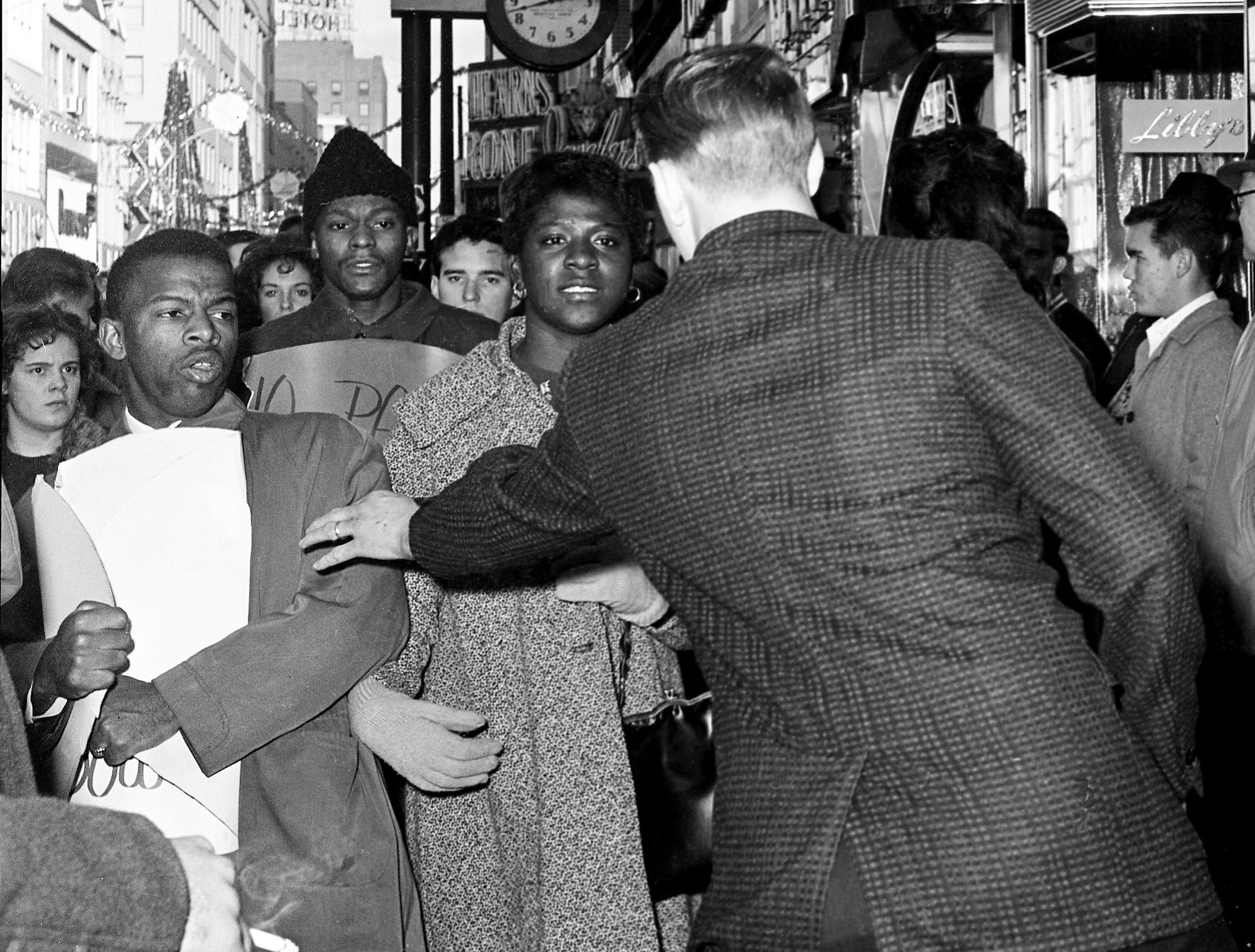 John Lewis, left, chairman of the local Non-Violent Committee, holds tightly onto his sign as a heckler reaches for him as Lewis and 12 other sit-in demonstrators try to get in the Herschel's Tic Toc restaurant on Church Street on Dec. 8, 1962. Behind Lewis is demonstrator Lester McKinnie.