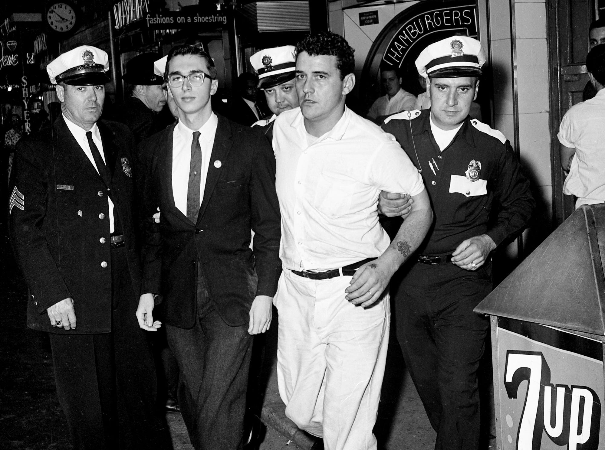 Nashville Police lead away sit-in demonstrator Jan Emmert and restaurant employee Bobby Gene Taylor after they were arrested at the Herschel's Tic Toc restaurant on Church Street on Dec. 1, 1962. Both were released after posting $5 bond each.