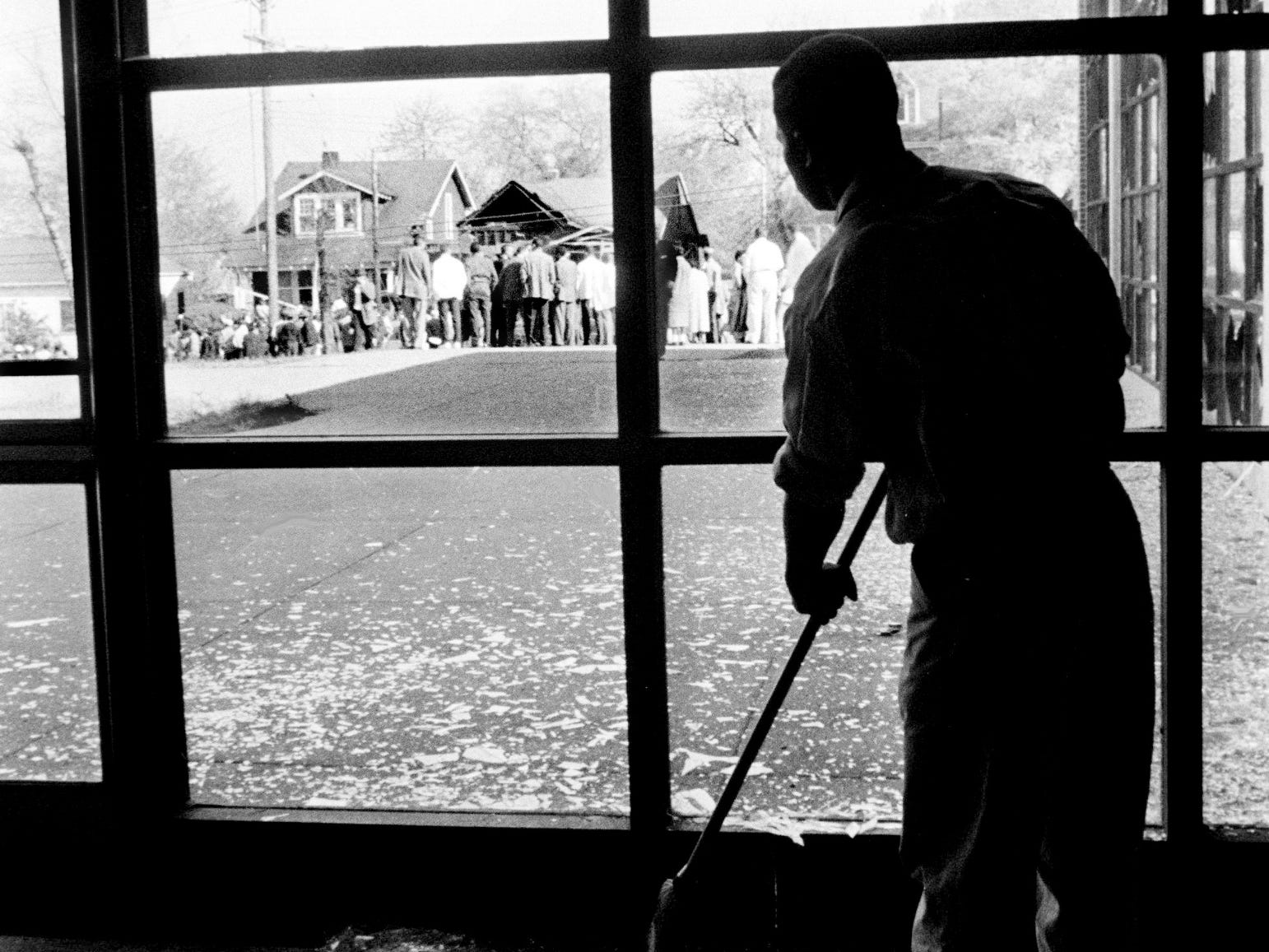 Silhouetted against disaster, John Thomas Martin wields his broom, sweeping up the fragments of glass from shattered windows in the Meharry Medical College Alumni building April 19, 1960. In the background, a curious crowd gathers at the bombed home of Z. Alexander Looby, which shattered 147 windows at the college.