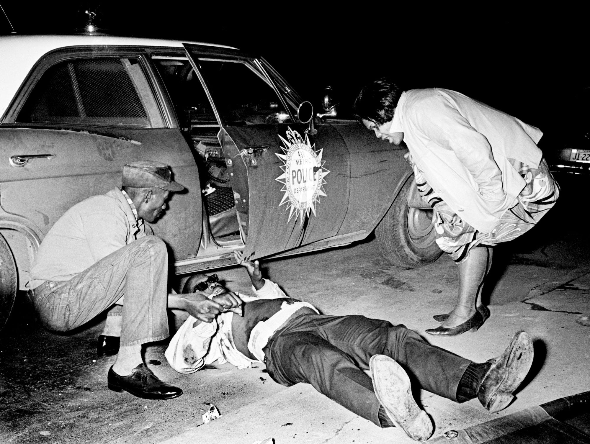 A couple of friends check on Elvis Fleming, center, after he was wounded during a Metro police gunbattle April 4, 1968. Fleming and 13-year-old Anthony Webster were hurt when police were summoned to 22nd Avenue and Osage Street to check on a complaint that an armed person was threatening residents during rioting after the assassination of the Rev. Martin Luther King Jr.
